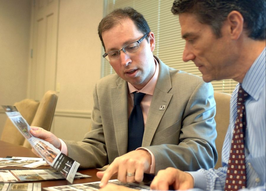 Fifth Third Bank area sales manager Evan Klee, left, and mortgage loan officer Russ Gelberg look over lists of local Realtors at their Highland Park bank.