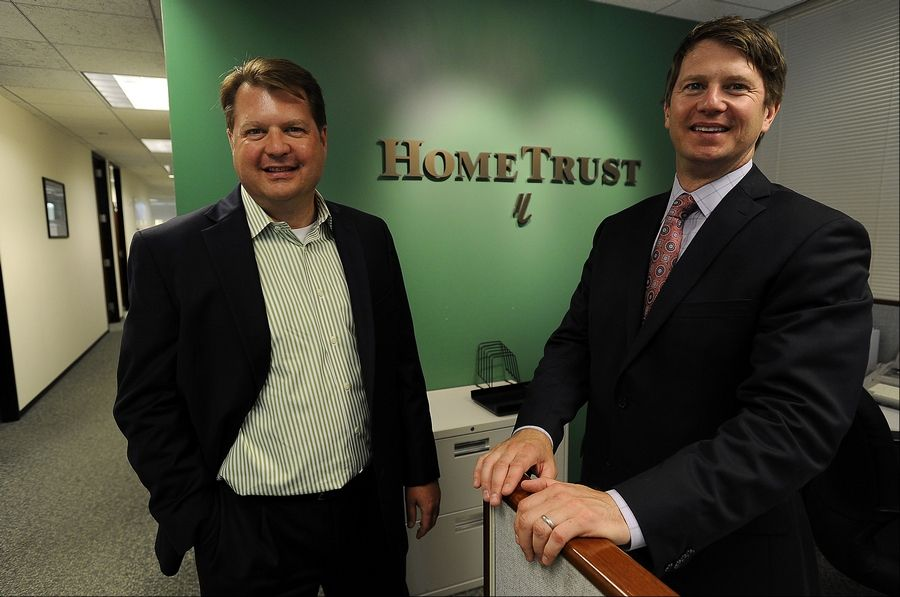 Evan Geiselhart, president at HomeTrust Mortage Corporation (left) in Schaumburg along with David Geiselhart, vice-president look over mortgage papers in their office as more people apply for mortgages.