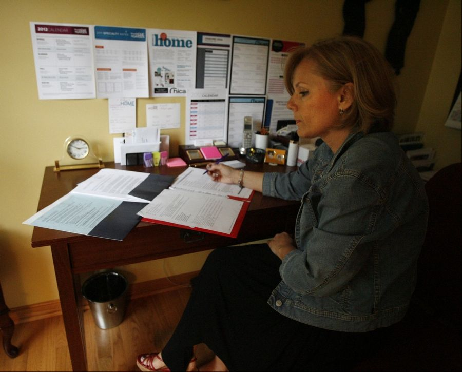 Valeria Coric reviews mortgage paperwork at her home in Lincolnshire. She and her husband locked in a lower rate when they refinanced to save month each month.