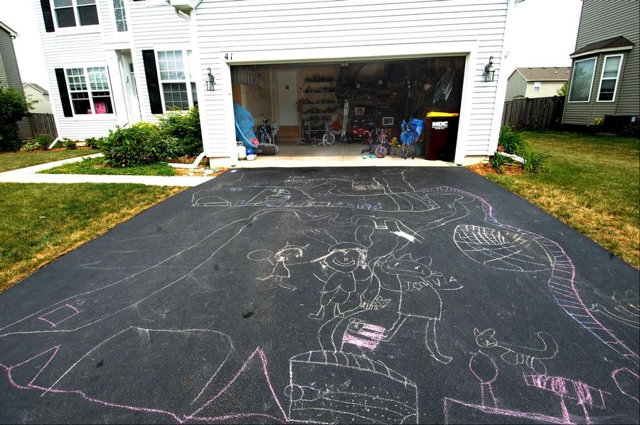 Scott and Pat Waldau refinanced their Gilberts home and are paying hundreds less on their monthly mortgage. Chalk artwork by their children decorates the driveway.