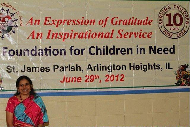 Dr. Geetha Yeruva, co-founder of FCN, stands with an anniversary poster at St. James Catholic Church in Arlington Heights.