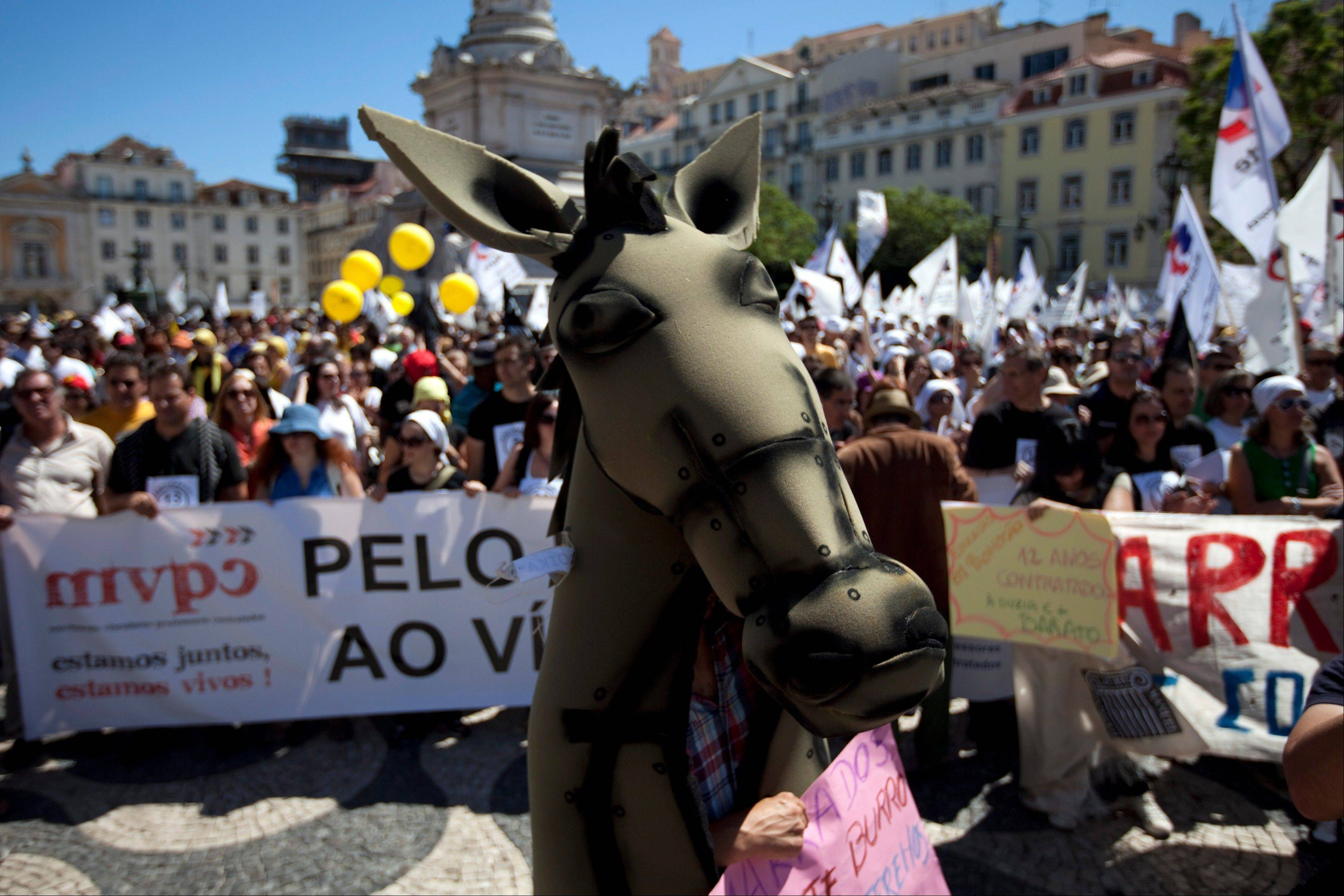 A protestor wearing a donkey costume walks among thousands of others gathered in Lisbon�s main Rossio square Thursday, during a teachers demonstration protesting the government�s education budget cuts. Concerns over Europe�s financial crisis weighed U.S. markets down Thursday.