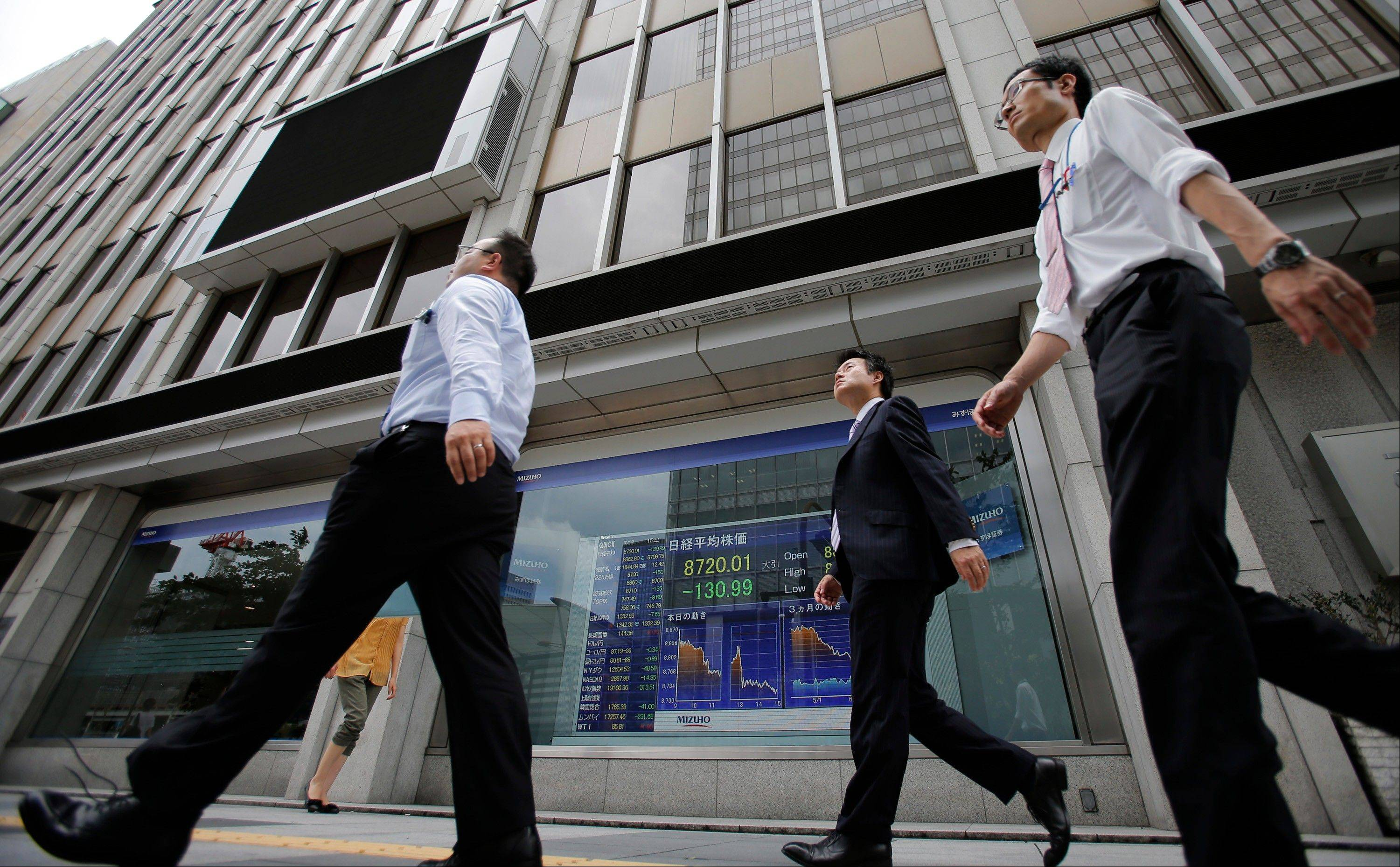 People walk past the electronic stock indicator of a securities firm in Tokyo Thursday.