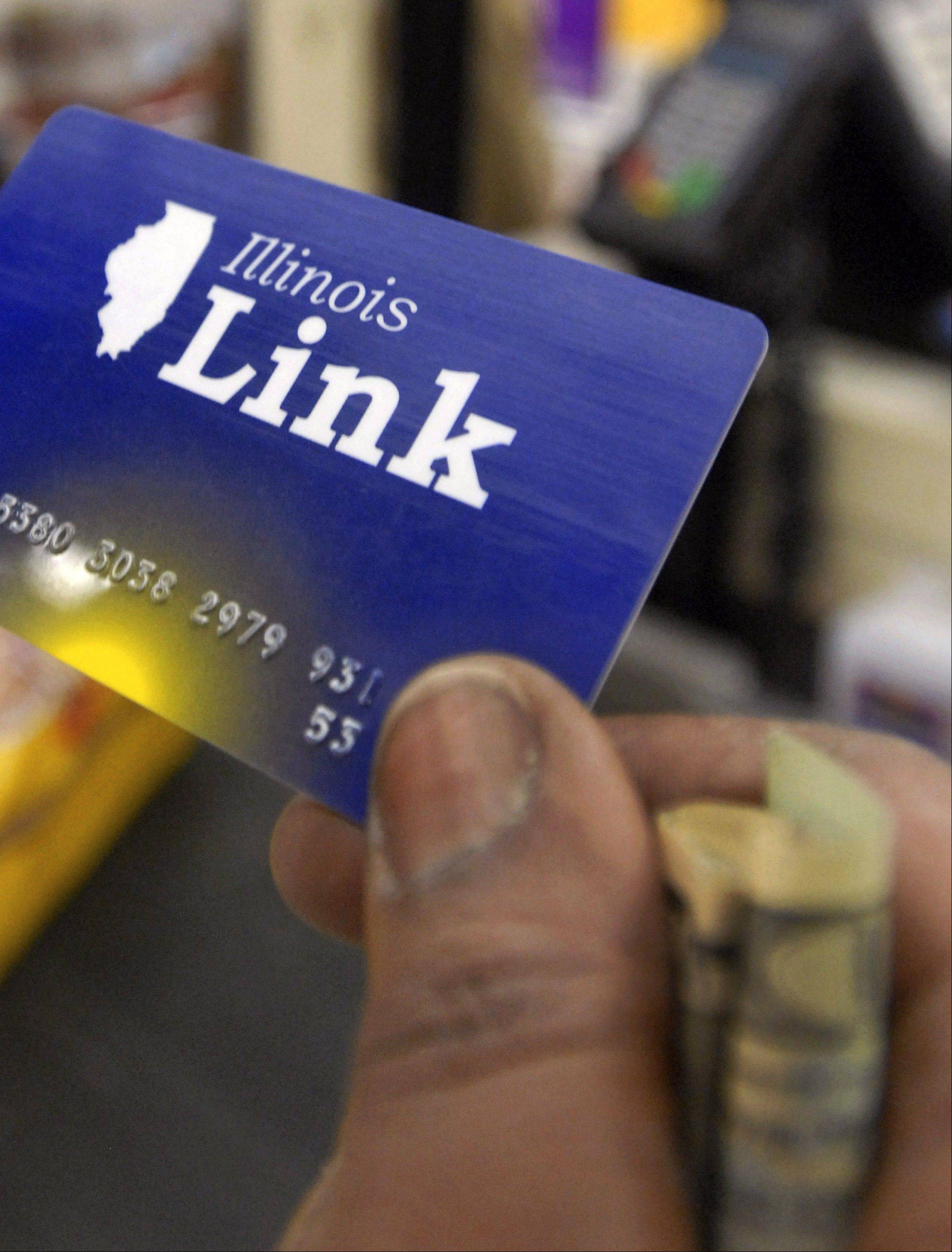 A customer holds a Link card, Illinois' version of food stamps, before paying for groceries at a store in Chicago.