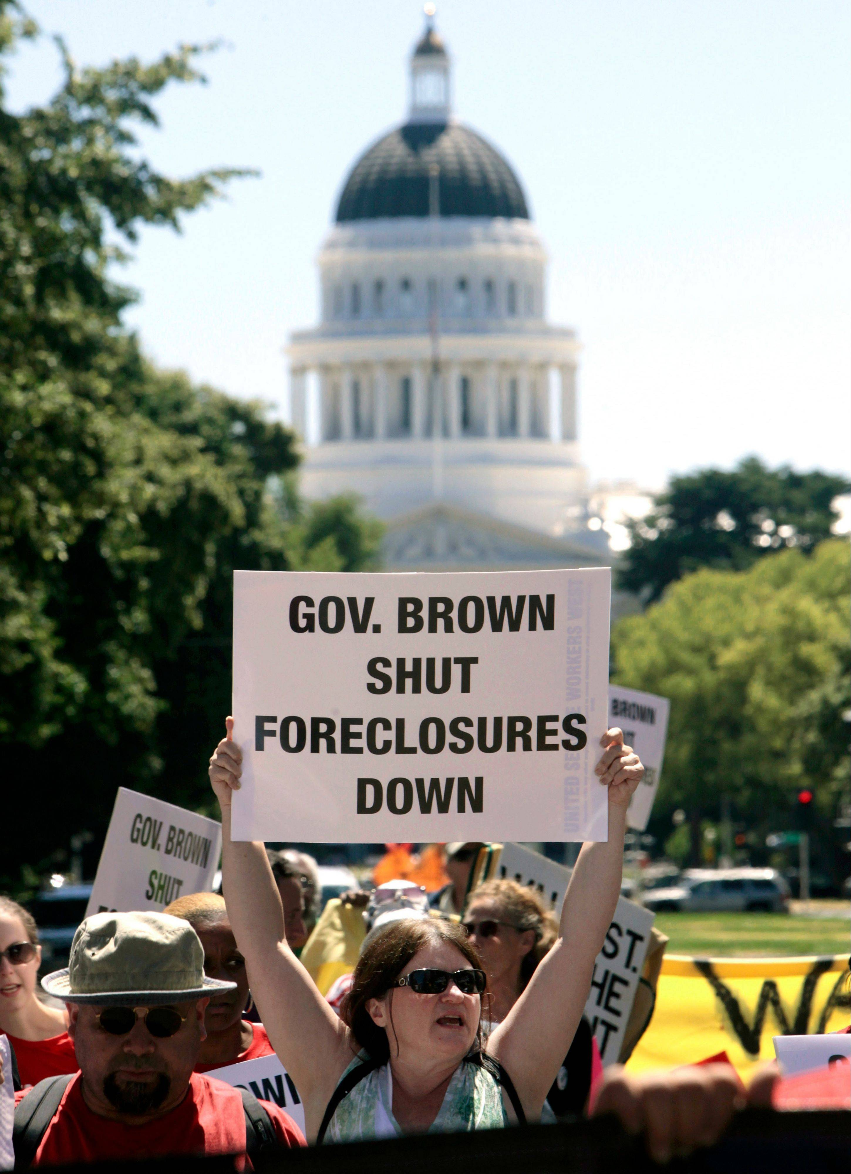 In this June 25, 2012 file photo, DeAun Tollefson, whose home is in foreclosure, joined others in a march at the Capitol to protest home foreclosures in Sacramento, Calif.