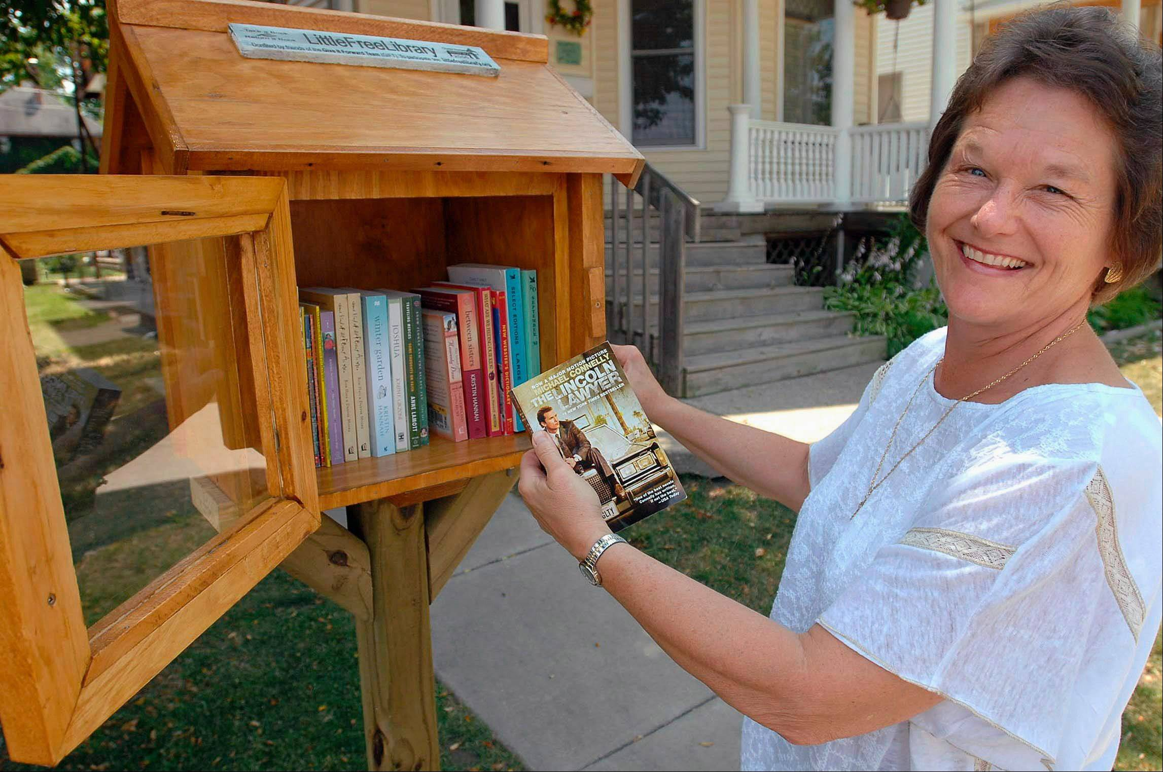 Tina Sipula stands outside the Clare House talking about the Little Free Library, a free book exchange, she put up outside the house she founded in Bloomington