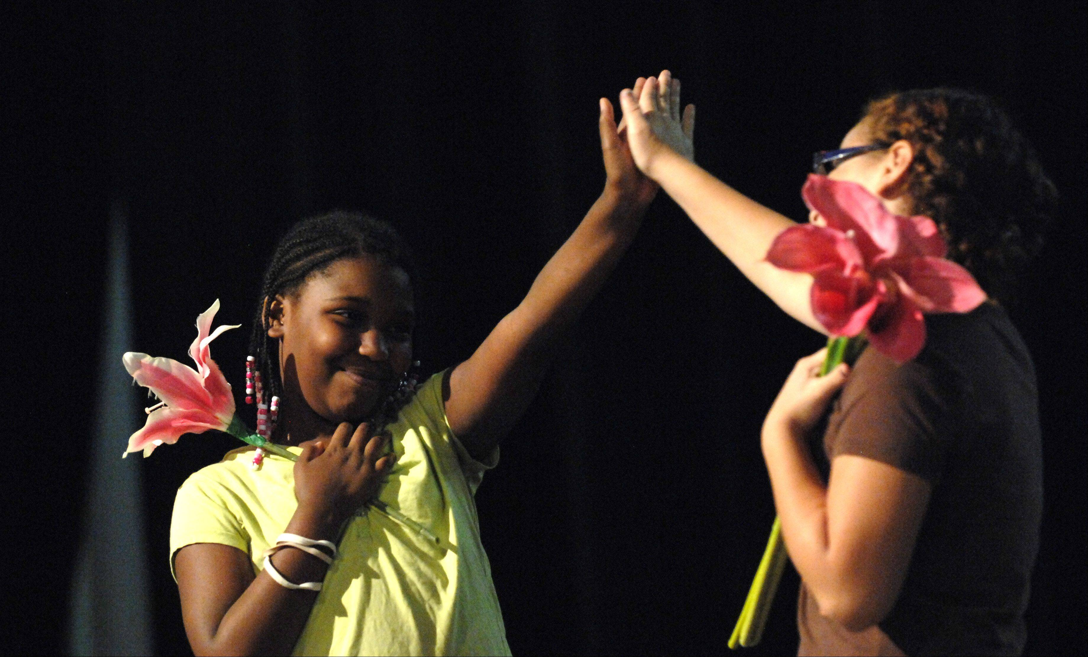 "Markeyah Johnson, 11, left, and Alexis Ruiz, 11, perform during a rehearsal of ""Destined Lives,"" an original opera created and produced entirely by 10-to-13-year-old students involved in Hamilton Wings' SCORE program. Johnson is from Elgin and Ruiz is from South Elgin."