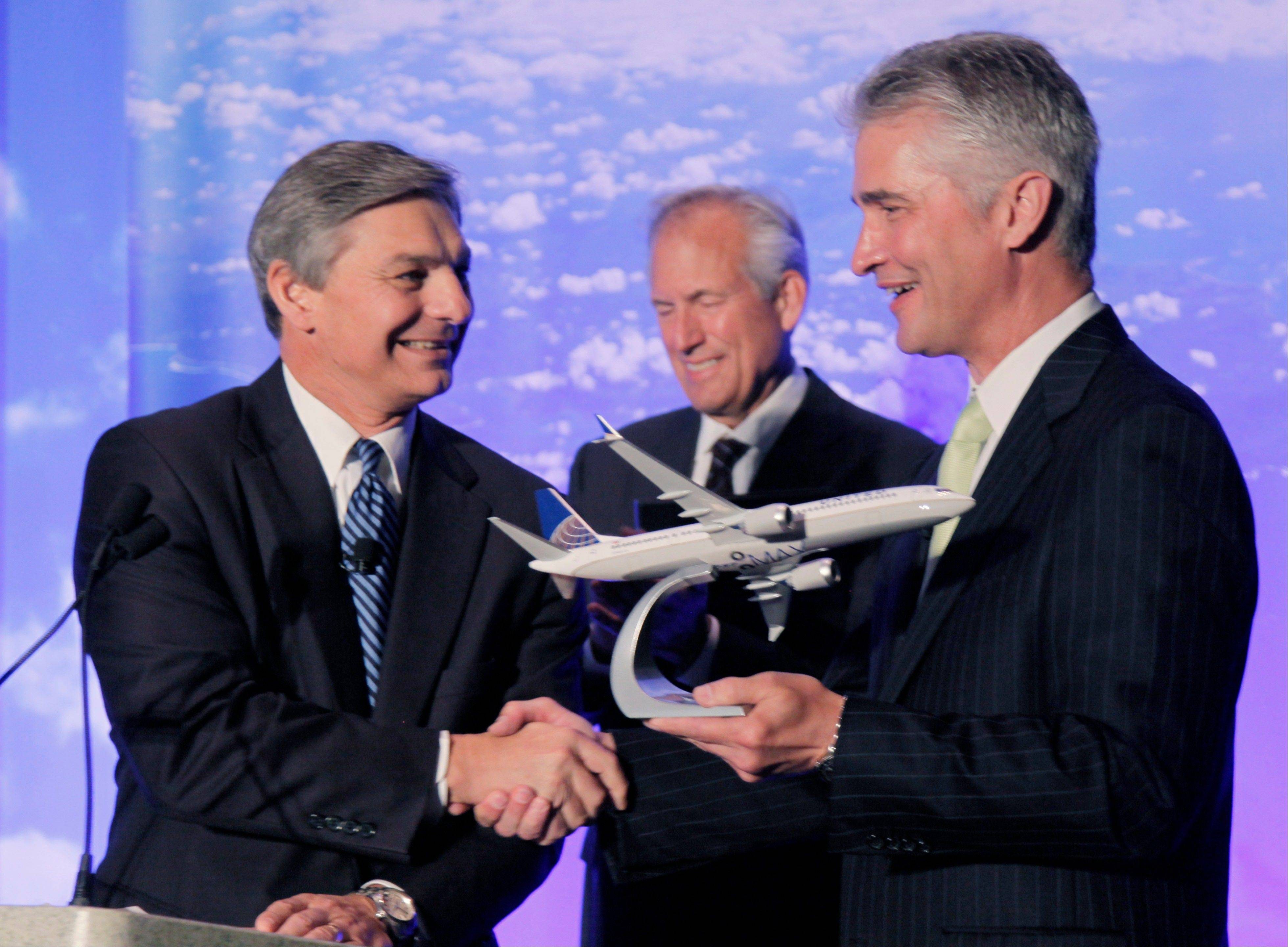 Boeing Commercial Airplanes CEO Ray Conner, left, presents a model of Boeing's new 737 Max 9 to United Airlines CEO Jeff Smisek during a news conference as Boeing CEO Jim McNerney looks on, Thursday in Chicago.