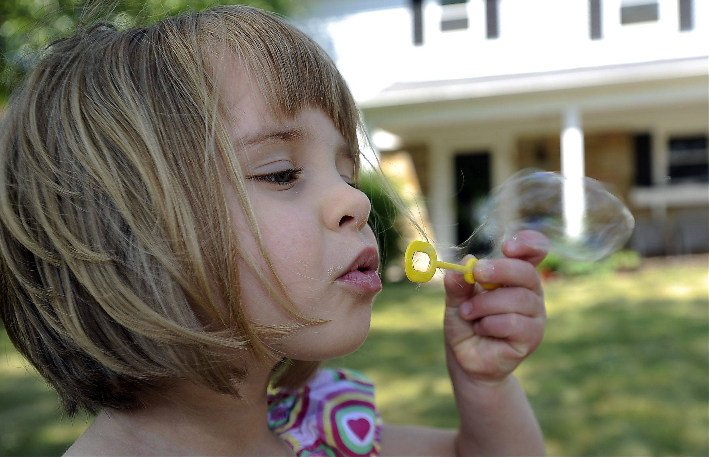 Lily Anderson, 4, enjoys blowing, and later catching, bubbles made from homemade solution.