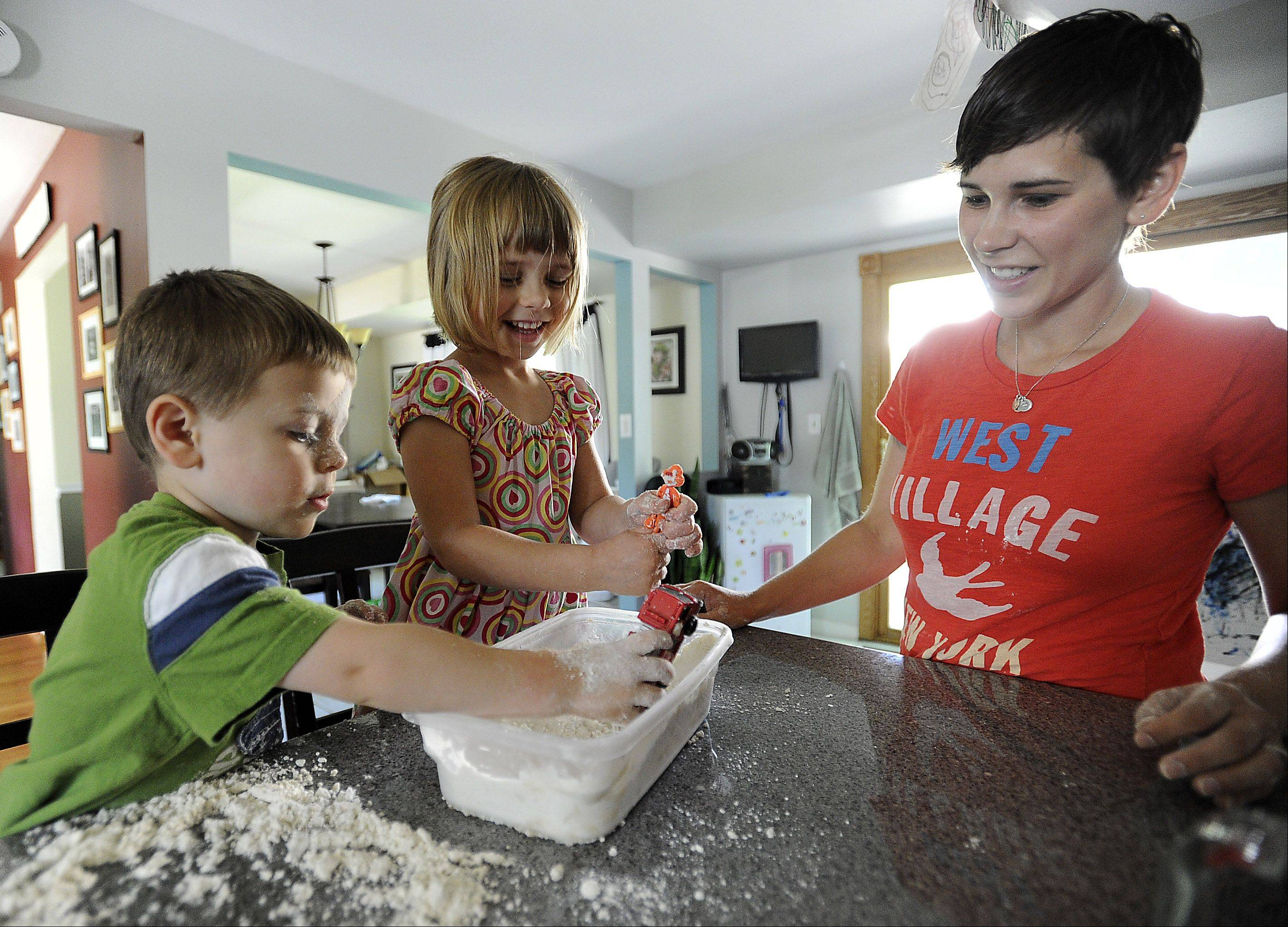 Author Rebecca Anderson of Schaumburg makes a homemade flour and baby oil mixture for her kids, Justin, 2, and Lily, 4.