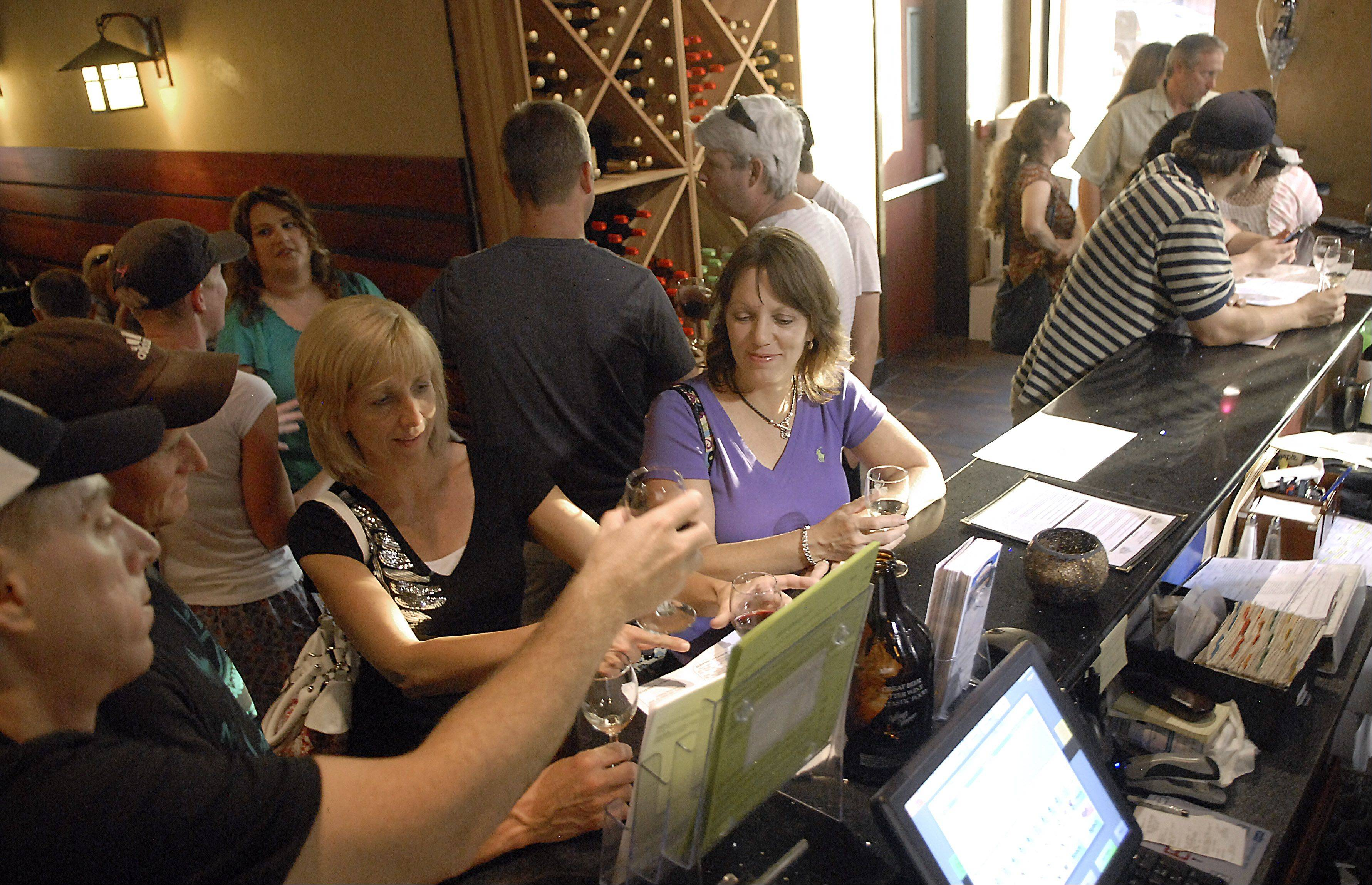 Customers check out the wine tasting at the Village Vitner in Algonquin.