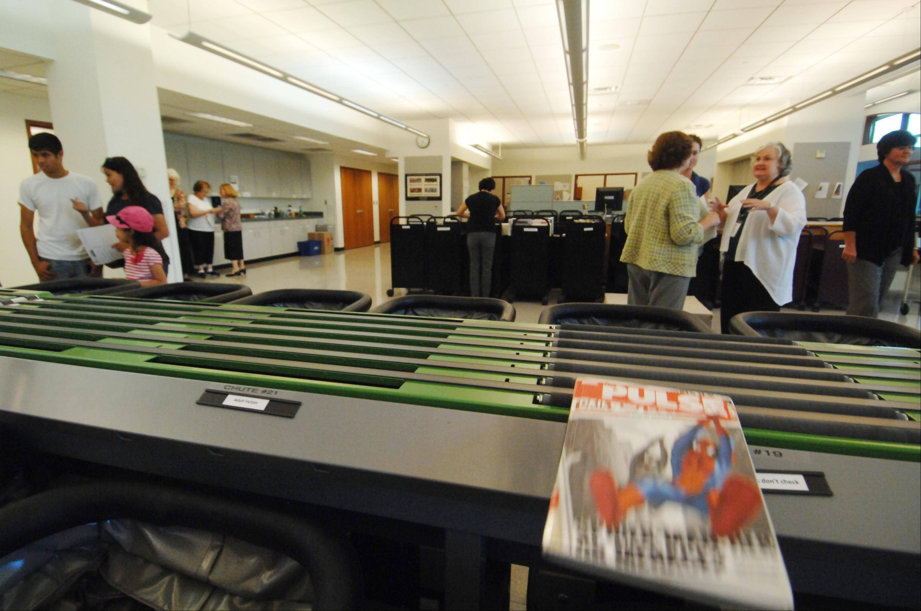 A book is automatically moved from the conveyor belt to a bin as a new sorting system works at the Gail Borden Public Library during a public demonstration Tuesday evening in Elgin. Library material can now be sorted and reshelved in minutes instead of days.