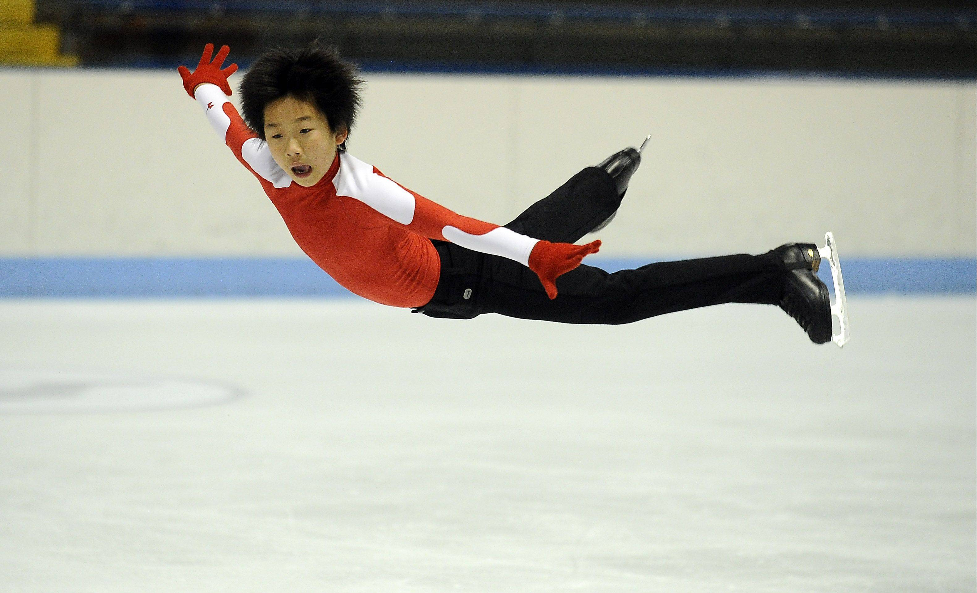 Hoffman Estates Olympic figure skating hopeful Tomoki Hiwatashi, 12, flies over the ice during a training session at the Centennial Ice Rink in Wilmette.