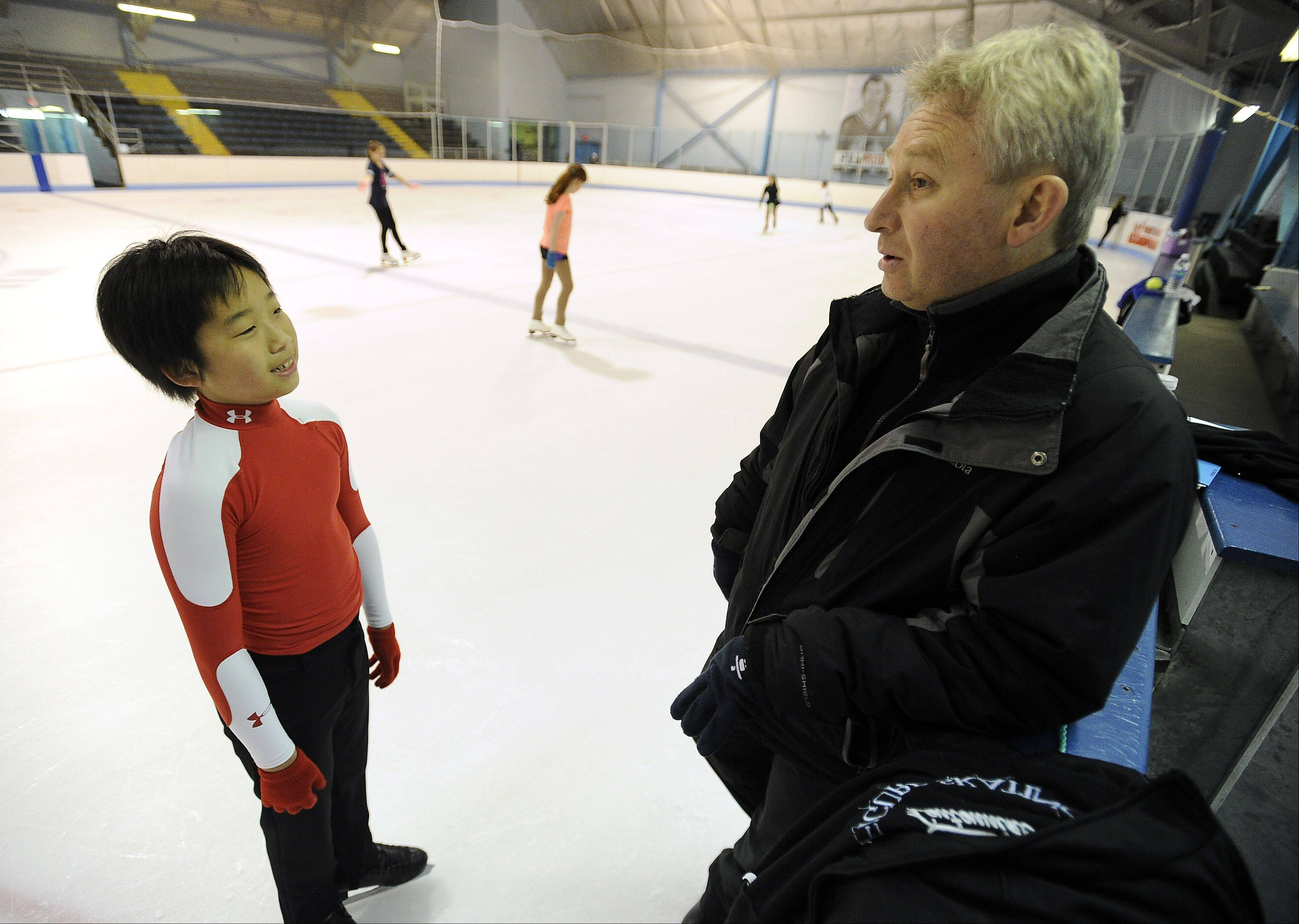 "Hoffman Estates Olympic figure skating hopeful Tomoki Hiwatashi, 12, talks with his coach, former USSR Olympian Alexandre ""Sasha"" Fadeev, during a training session at the Centennial Ice Rink in Wilmette."