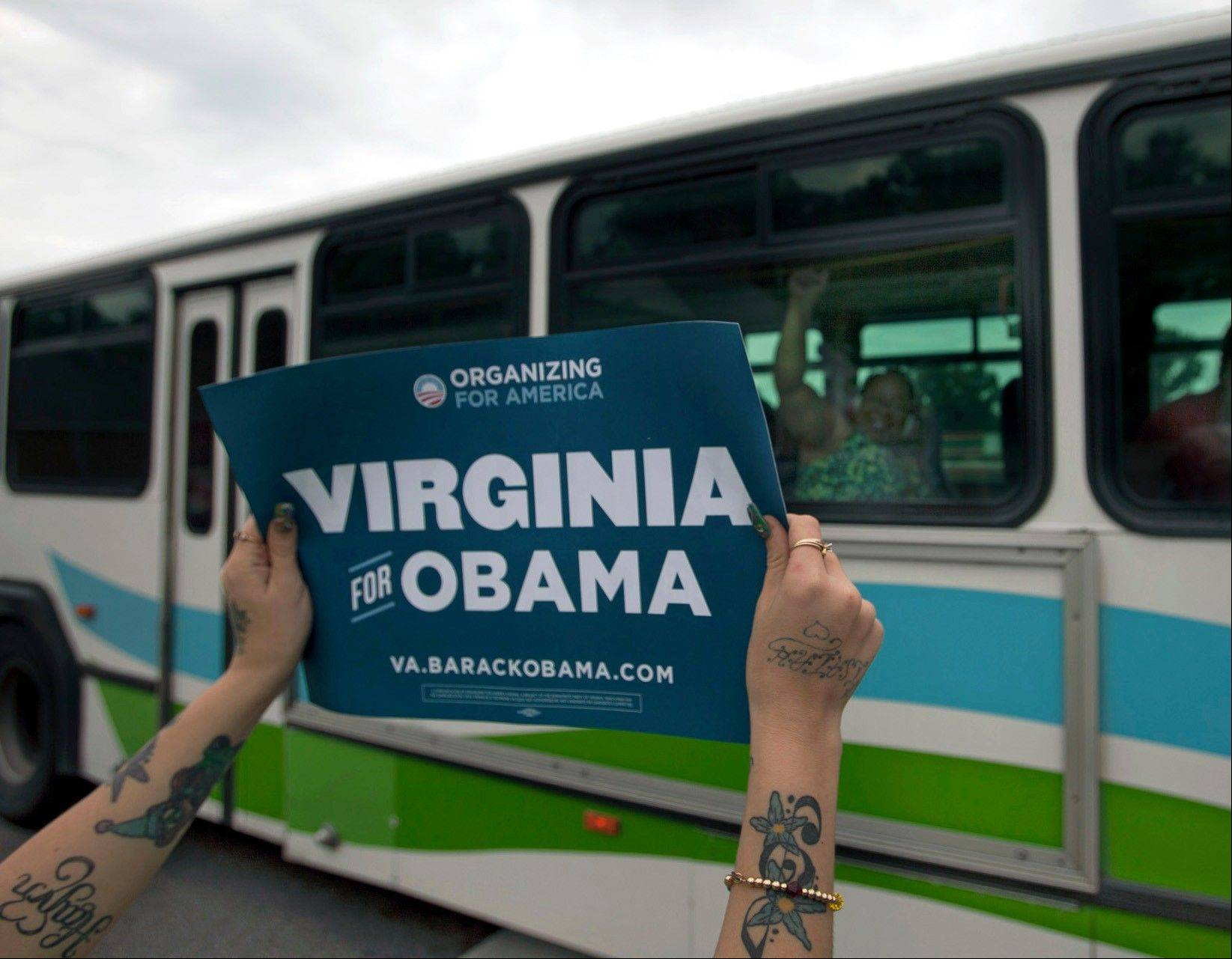 A person holds a sign in support of President Barack Obama along S. Independence Boulevard at Edwin Drive Wednesday, July 11, 2012, in Virginia Beach, Va., as people wait in line for tickets to see the president Friday at Green Run High School.