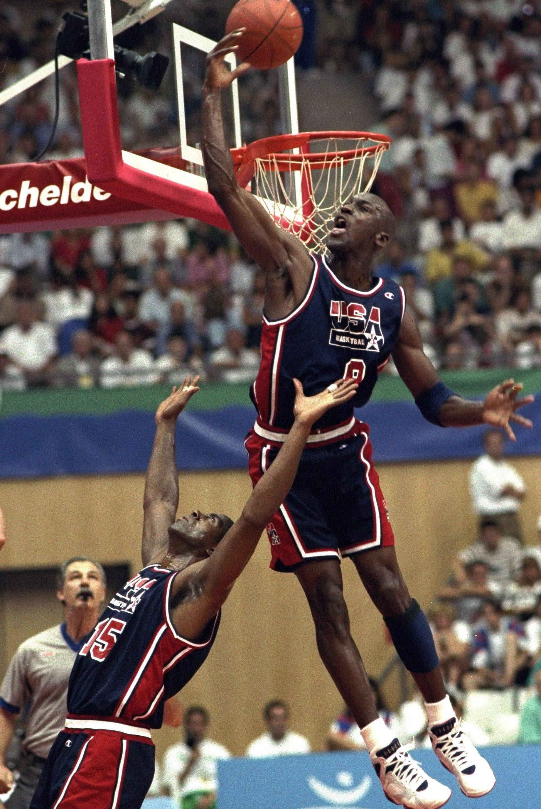 USA's Michael Jordan sails high above teammate Magic Johnson, knocking away a shot during the first half of their preliminary-round basketball game with Croatia at the Summer Olympics in Barcelona in 1992.