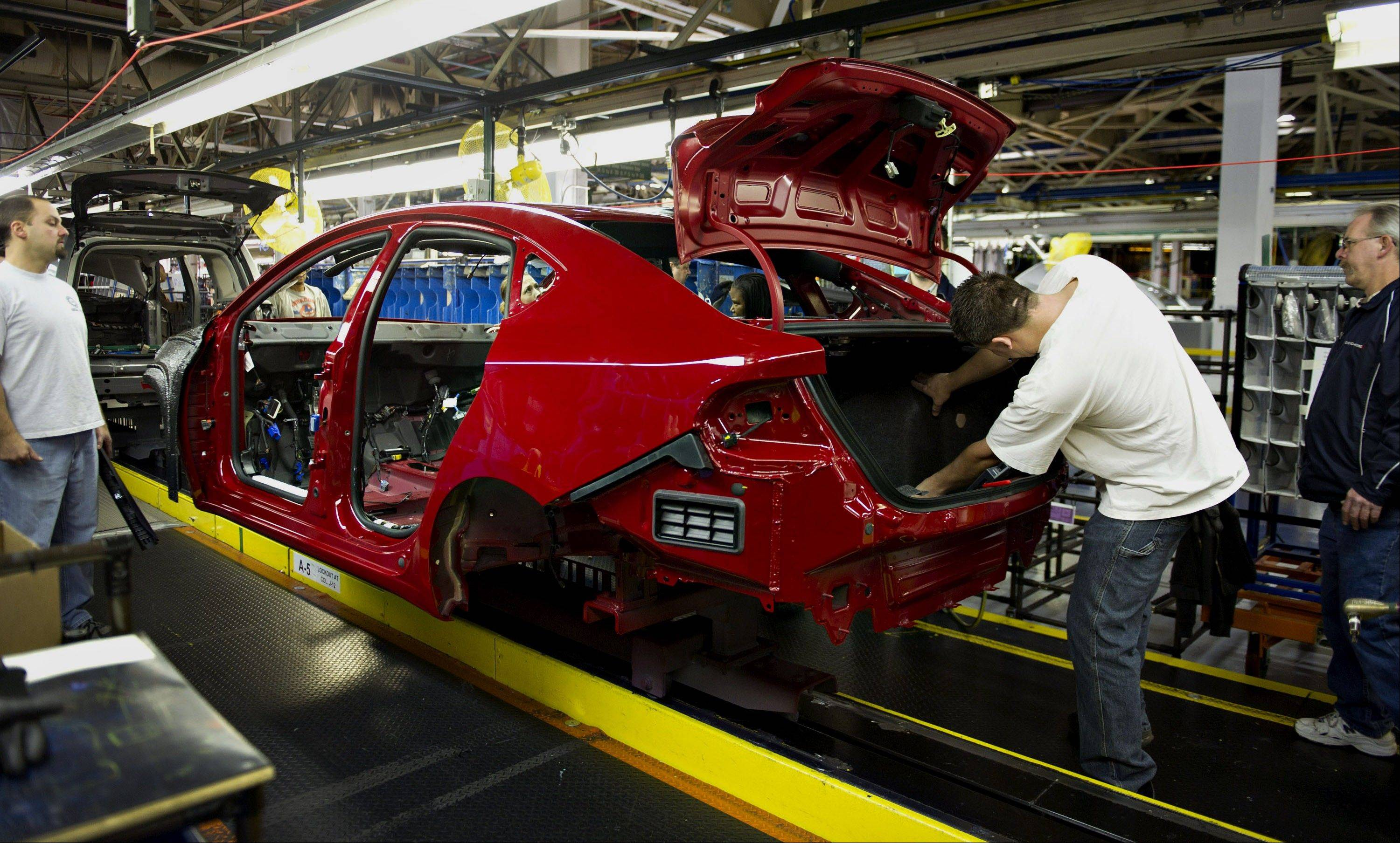 Chrysler Group LLC employees work on a 2013 Dodge Dart as it moves along the production line at the company's assembly plant in Belvidere, Illinois, U.S., on Thursday, Feb. 2, 2012. Chrysler announced it will add 1,800 more jobs at the Belvidere plant, nearly 500 .
