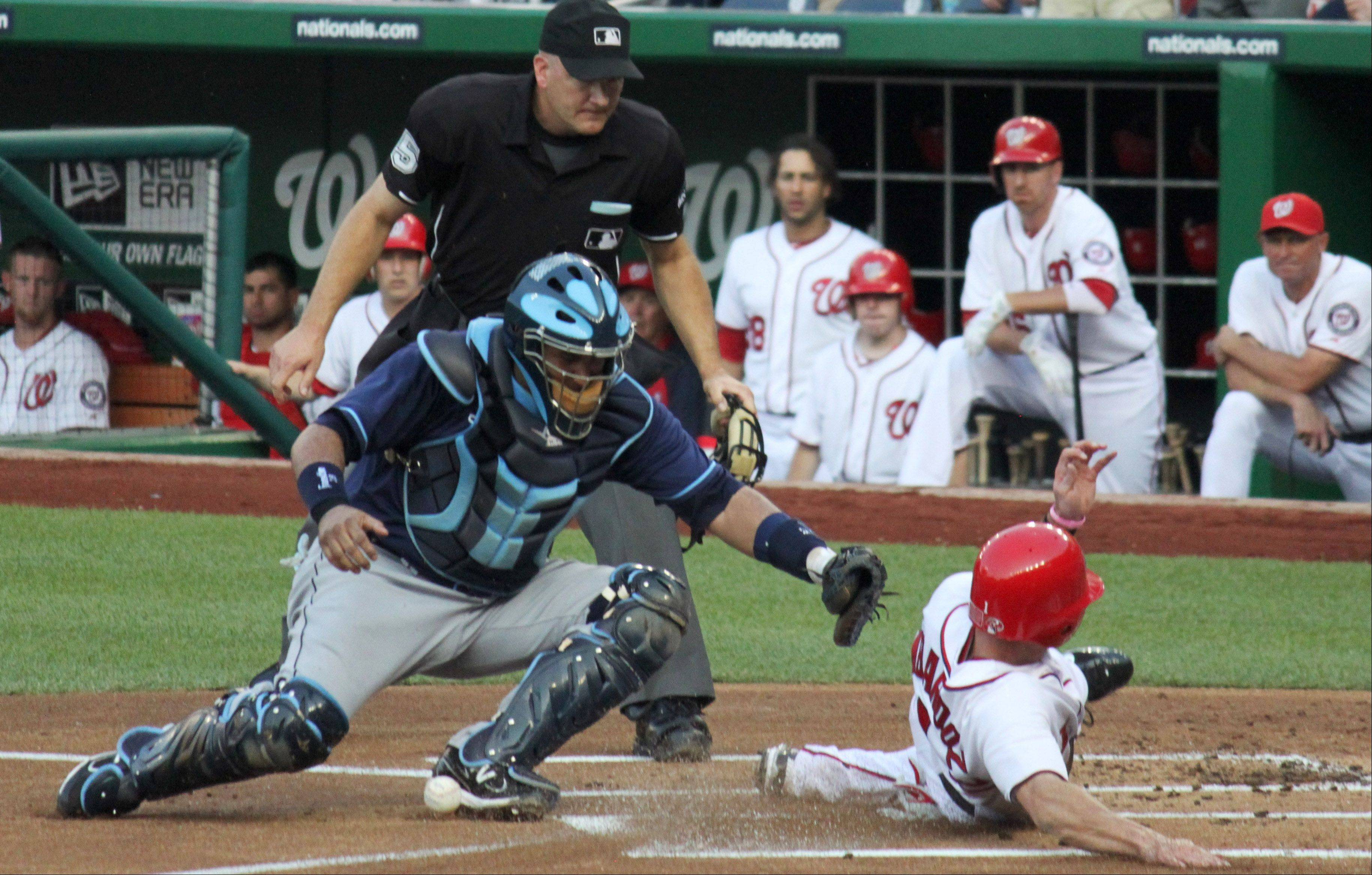 Steve Lombardozzi slides home safely as the ball lays at the feet of Tampa Bay catcher Jose Molina during a baseball game between the Washington National and Tampa Bay Rays in Washington, D.C. on June 20.