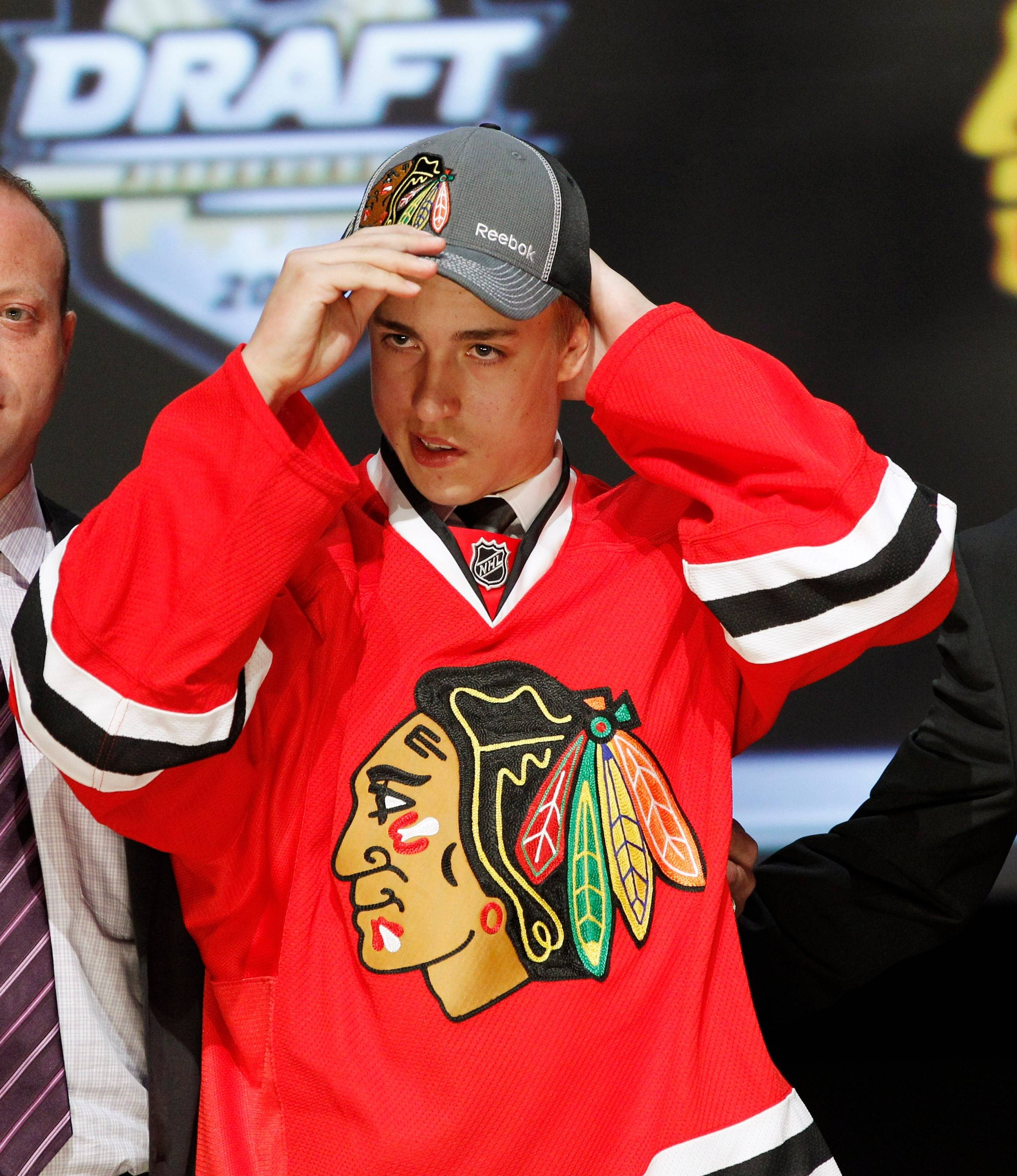 Teuvo Teravainen of Finland puts on a Blackhawks cap and jersey after being selected as the team's first-round draft pick in June.
