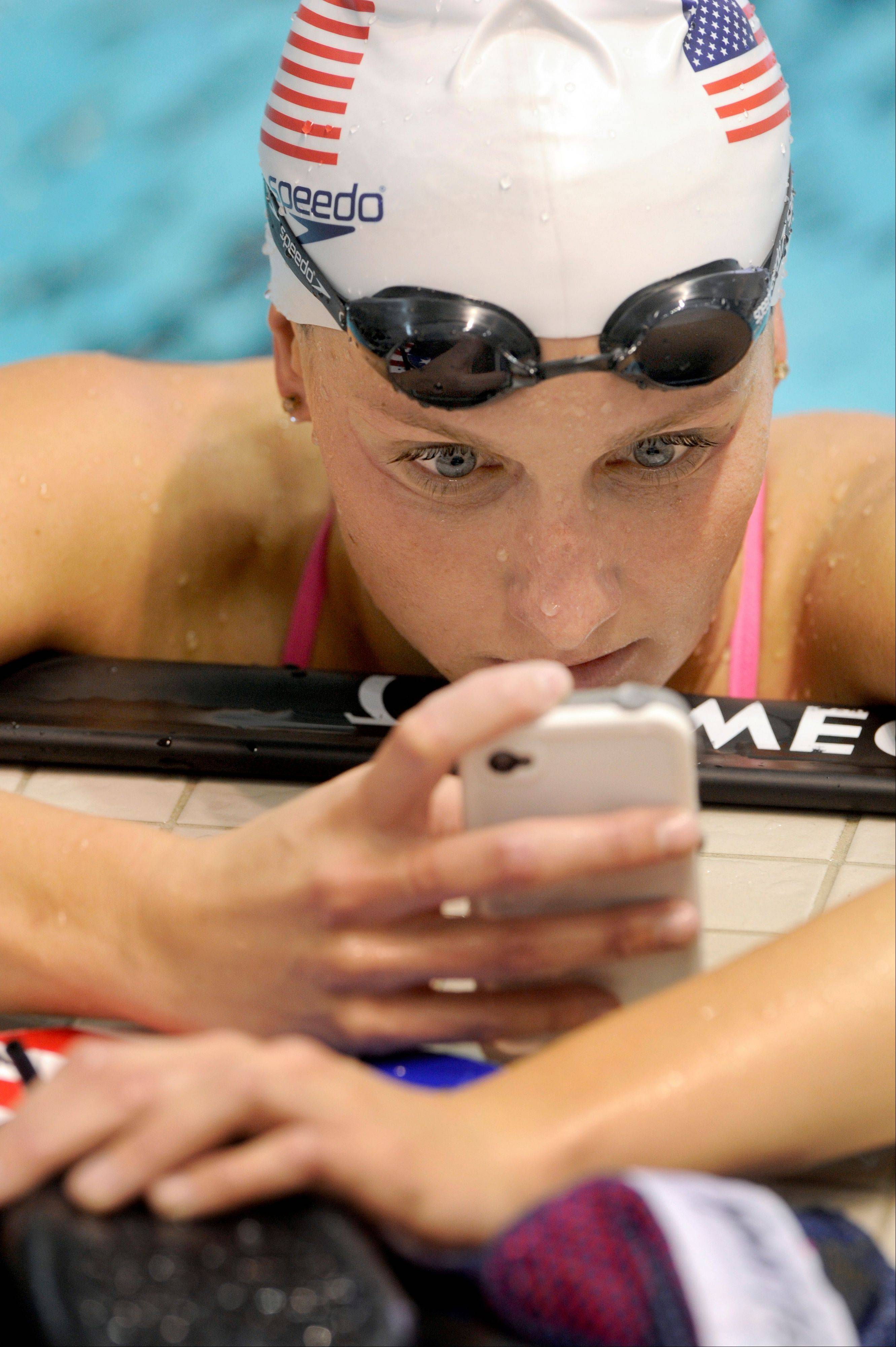U.S. Olympic swim team member Kara Lynn Joyce checks her phone between practice laps Thursday at the University of Tennessee's Allan Jones Aquatic Center. NBC is offering two free mobile apps for the London Games.