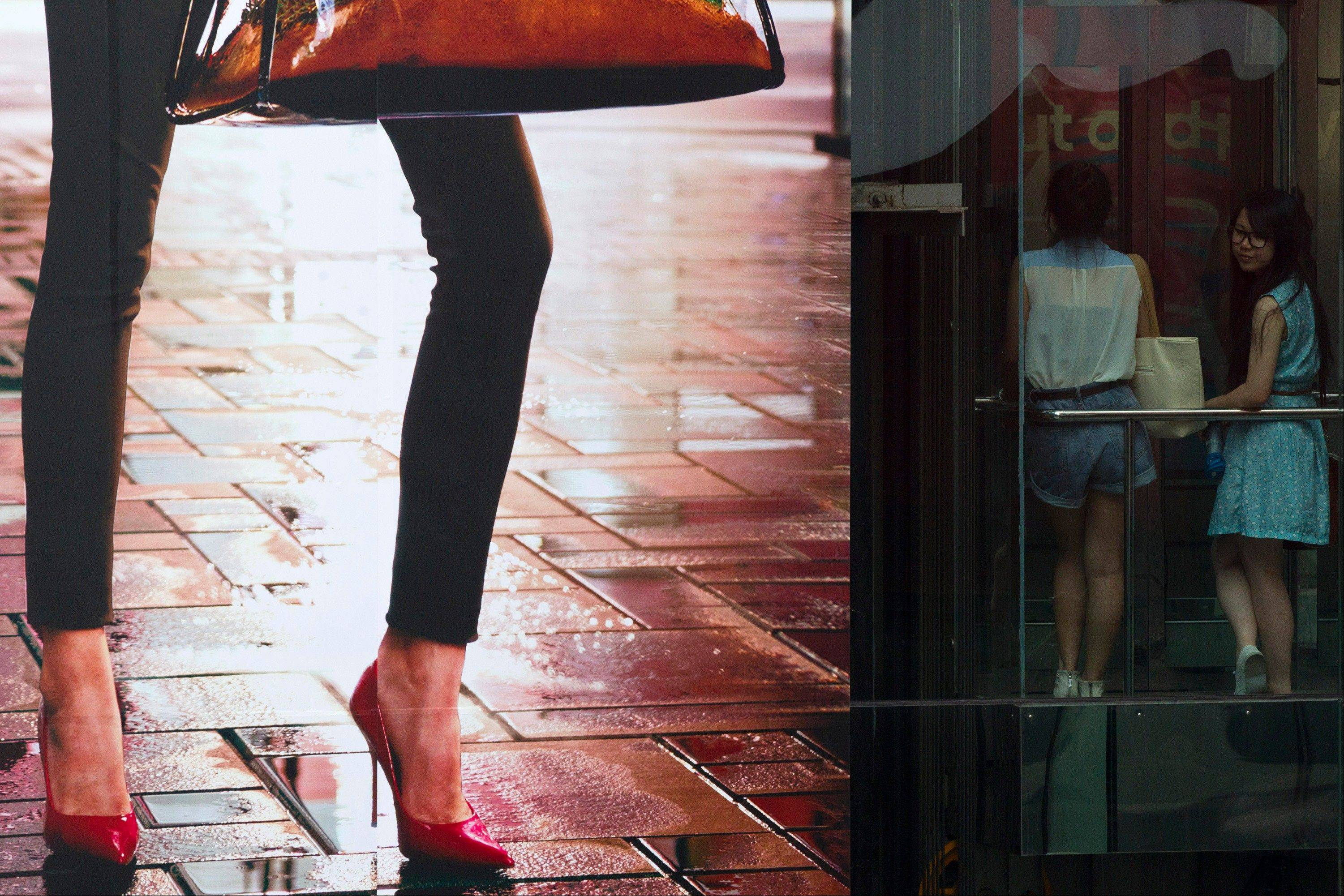 Two women stand in a lift near an advertisement board in Beijing's Central Business District on Wednesday. China's latest economic data indicate a deepening slowdown that is adding to pressure on communist leaders to revive growth and avert job losses and political tensions.
