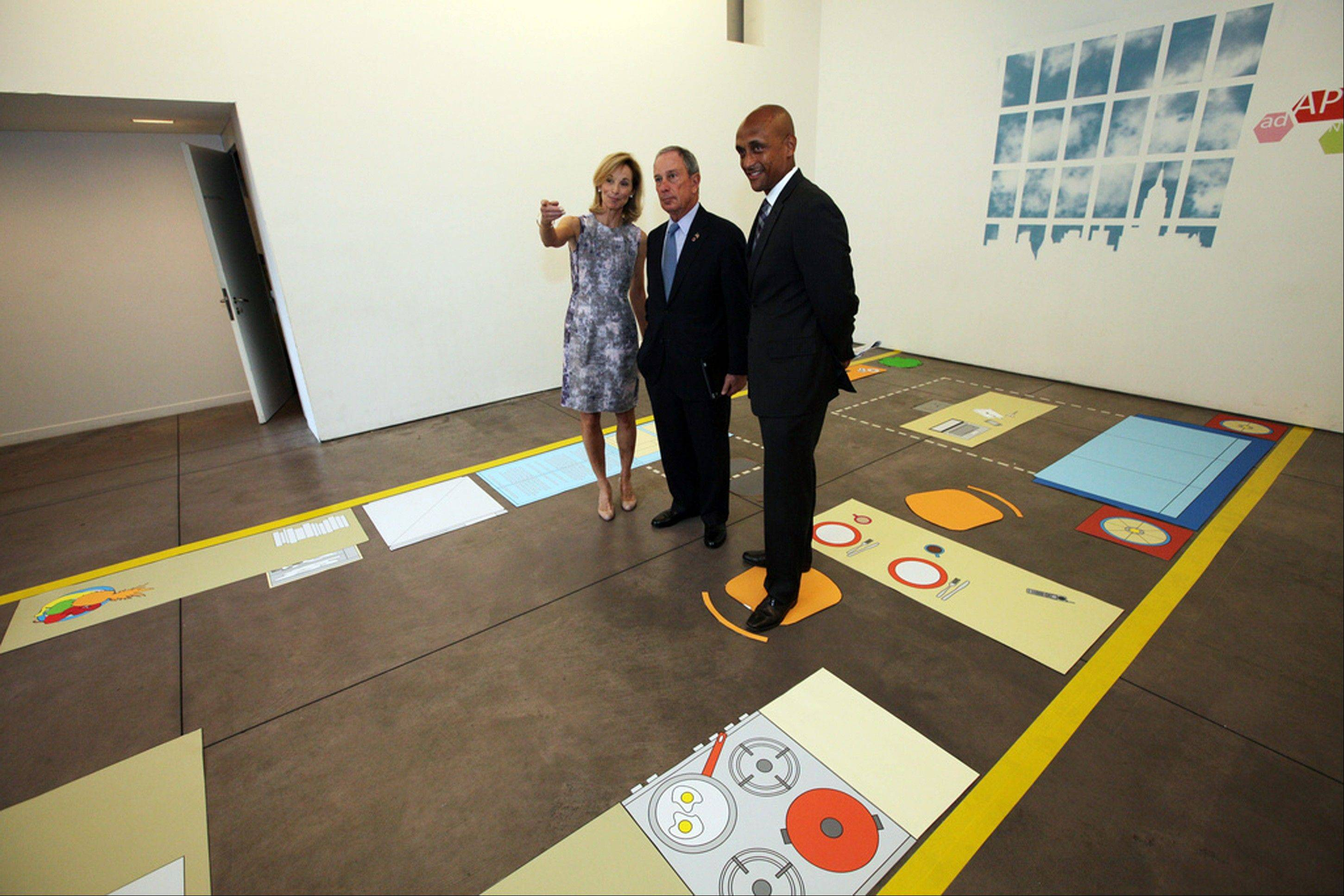 In this photo provided by the New York mayor's office, Mayor Michael Bloomberg, center, stands with Amanda Burden, left, department of city planning director, and Commissioner Mathew Wambua, department of housing preservation and development, in the kitchenette area of a full-scale mock-up of a 300-square-foot-apartment on Monday in New York. The city is asking developers to propose ways to build such tiny units in the hopes of changing city code to accommodate cash-strapped singles and couples.