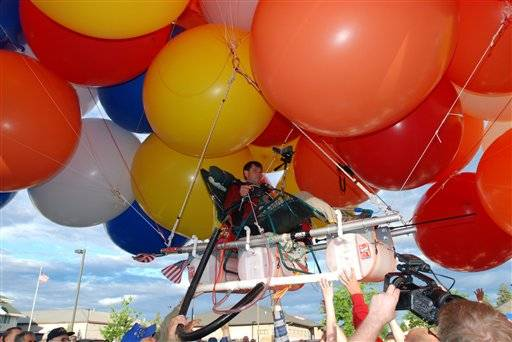 "This photo shows Kent Couch in 2008 lifting off from his gas station in Bend, Ore., riding a lawn chair rigged with more than 150 giant party balloons for a flight that ended 235 miles away in an Idaho farm field. Oregon's ""lawn-chair balloonist"" has put off his flight in Iraq until next year. Couch had planned another balloon flight Tuesday, Nov. 15, 2011 in Baghdad along with Iraqi daredevil Fareed Lafta. But a statement Monday from spokesman Mark Knowles says the two have delayed the flight until March to accommodate a number of groups that want to use it to raise awareness of the plight of Iraqi orphans."