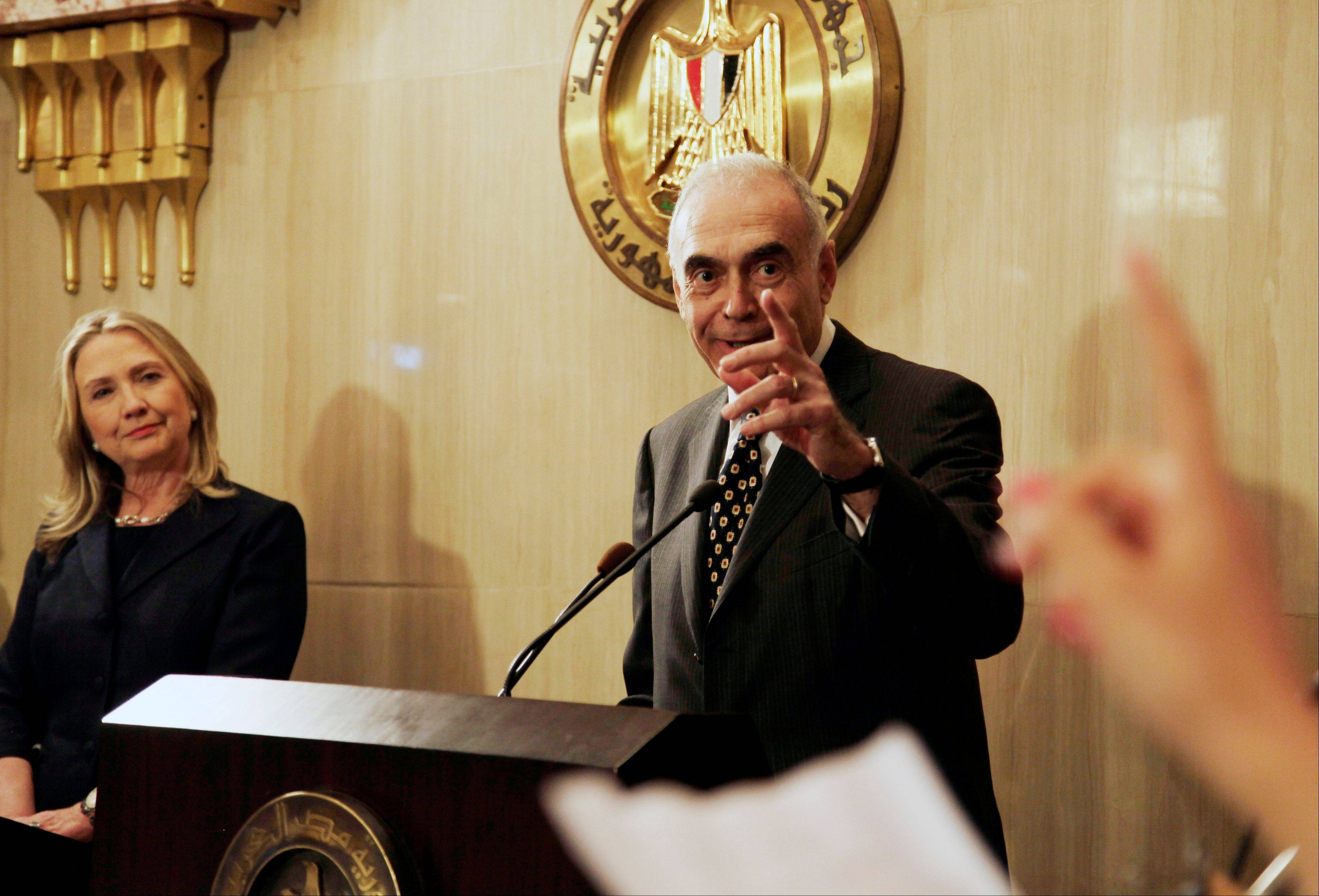 Egyptian Foreign Minister Mohammed Kamel Amr, right, takes a reporter's question Saturday at a joint press conference with U. S. Secretary of State Hillary Rodham Clinton at the presidential palace in Cairo, Egypt.