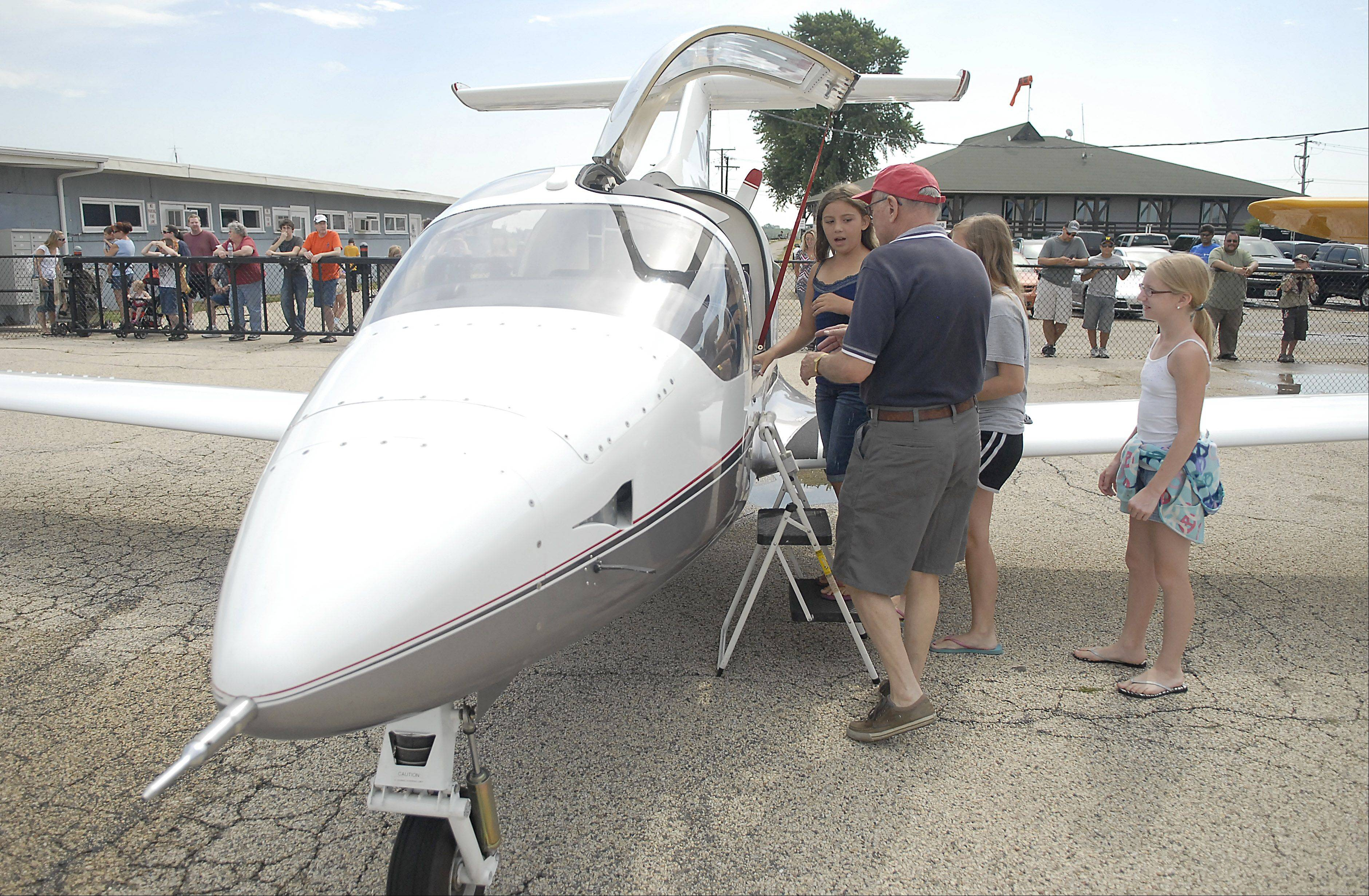 Ole Sindberg of Cary helps Lexi Yates, 9, of Crystal Lake into his Prescott Pusher personal aircraft Saturday for a free flight at the Lake in the Hills Airport. The Young Eagles event offered free flights for children ages 8 to 17 through the EAA Chapter 790.