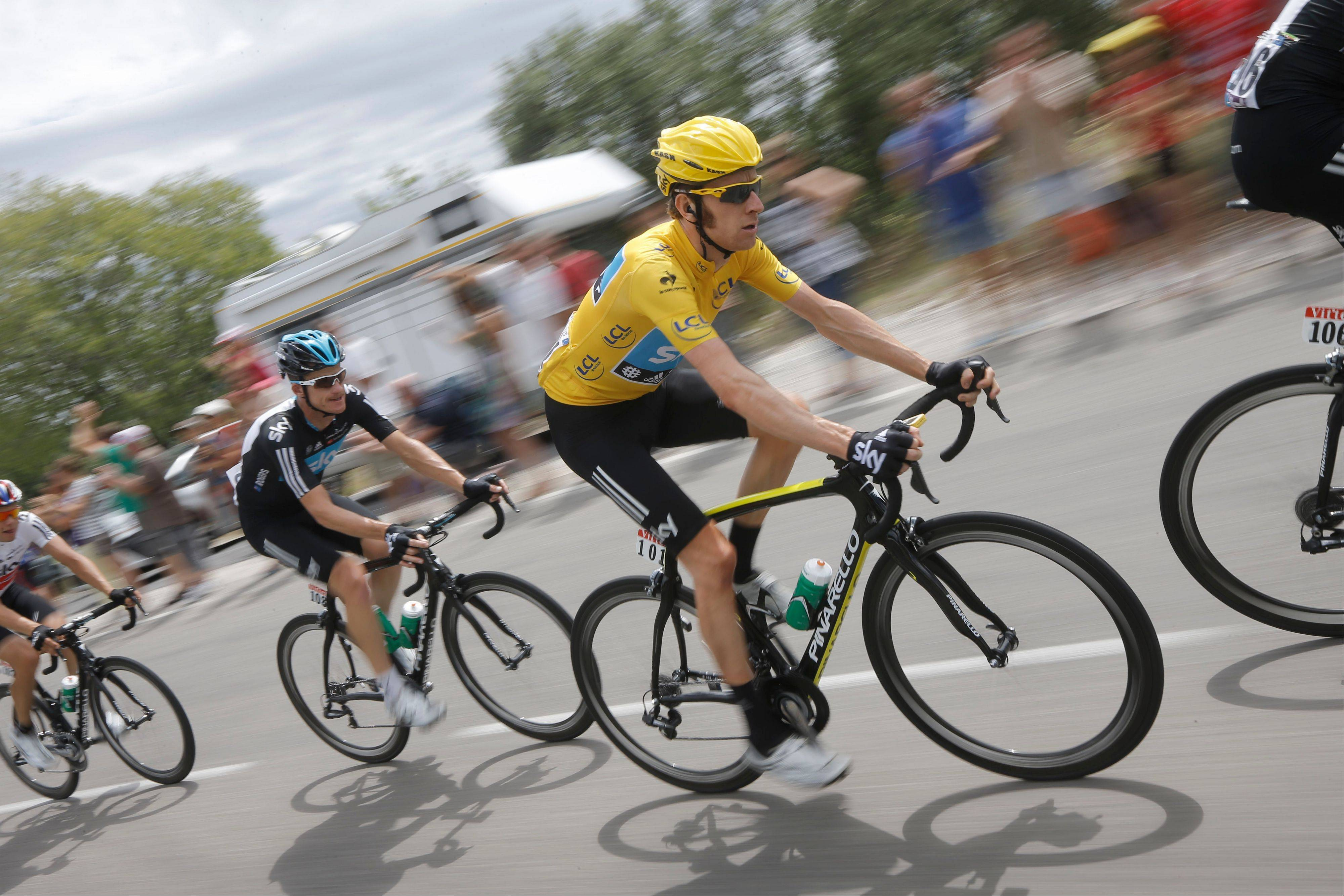 Bradley Wiggins, wearing the overall leader's yellow jersey, rides in the pack Saturday during the 13th stage of the Tour de France.