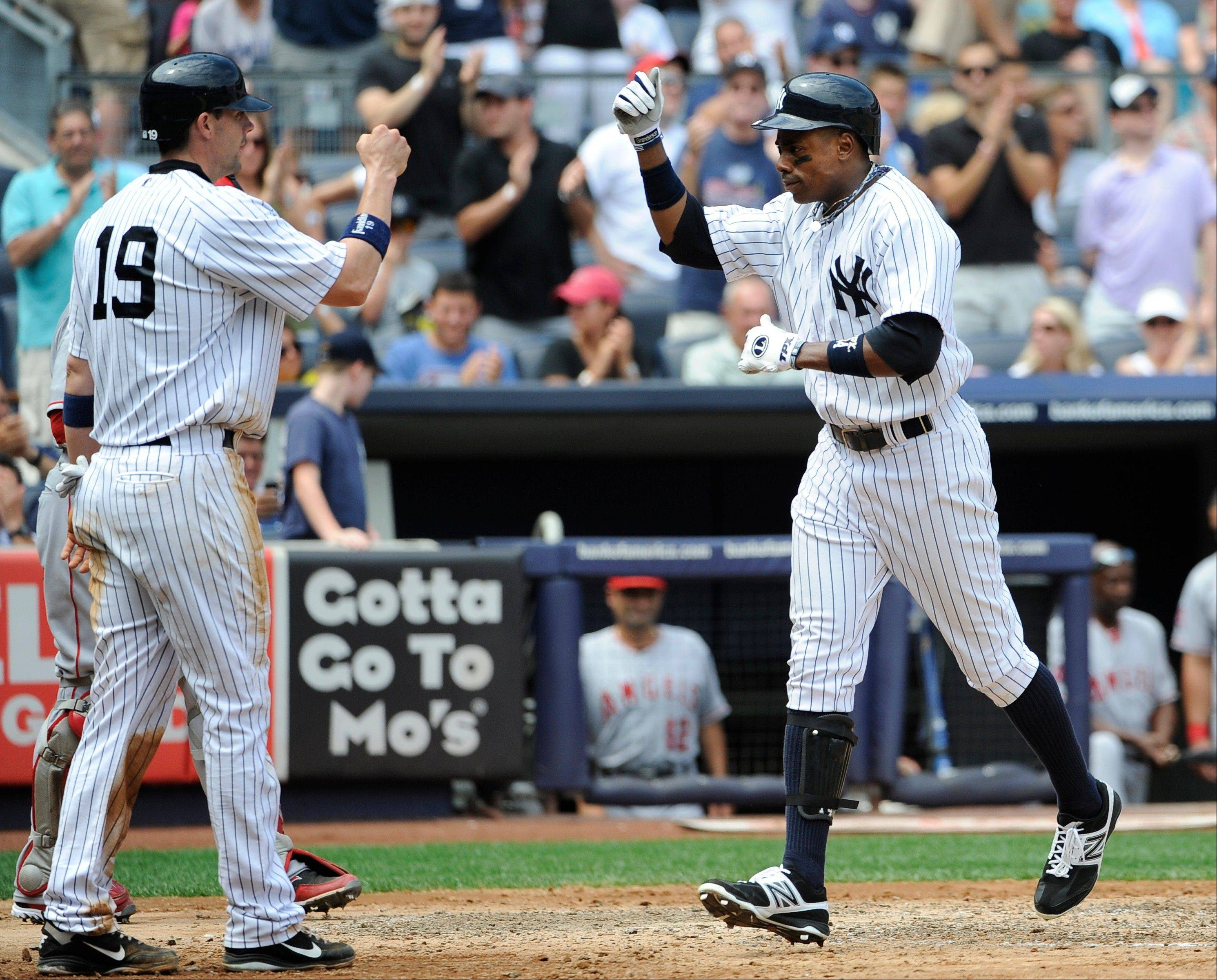The New York Yankees' Chris Stewart (19) greets Curtis Granderson at home plate Saturday after Granderson hit a two-run home run off Los Angeles Angels starting pitcher Jerome Williams in the third inning at Yankee Stadium in New York. The Yankees won 5-3.