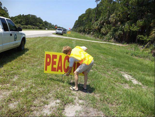 Volunteer code enforcement officer Joyce Case removes a sign from the roadway. Case has volunteered to help find code violations.