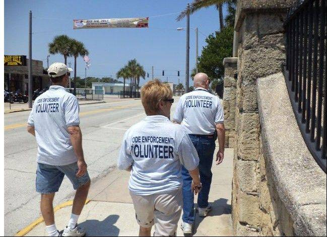 Volunteer code enforcement officers, from left, Brian Case, Joyce Case and John McCarthy walk the community in search of code violations June 30. The patrol was part of their training.