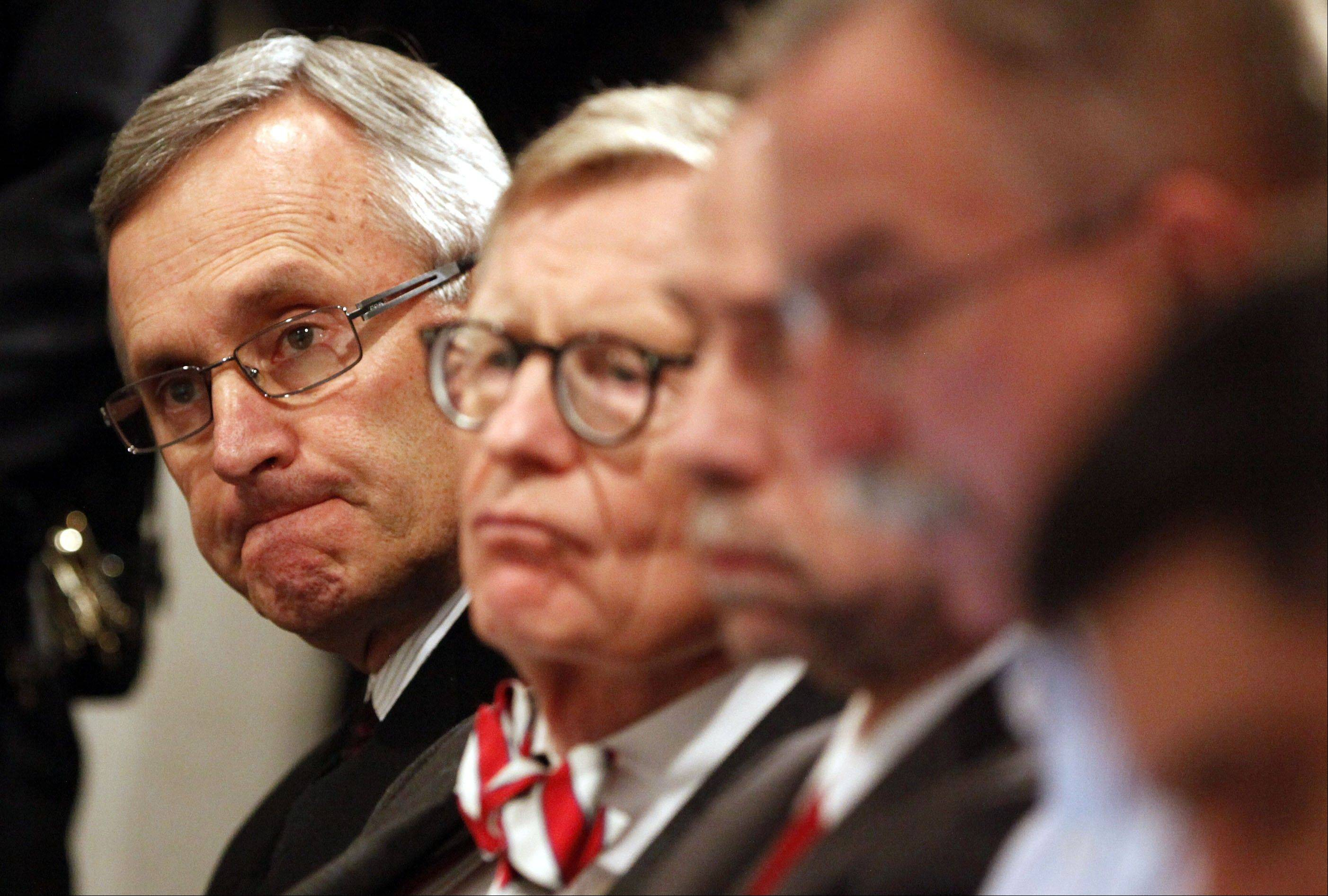 Ohio State football coach Jim Tressel, left, and university President E. Gordon Gee, second from left, listen as athletic director Gene Smith speaks during a news conference in Columbus, Ohio.