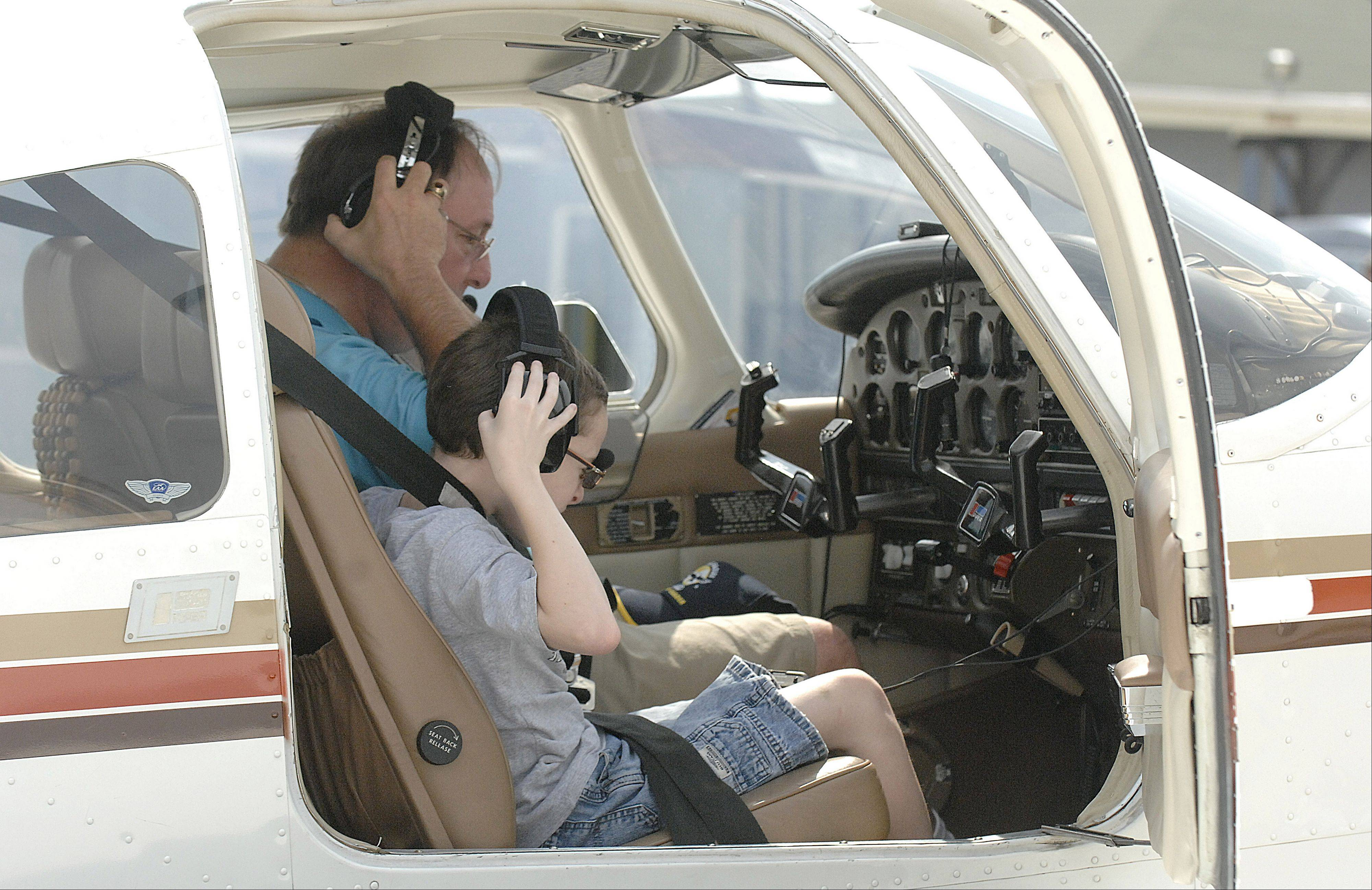 Robert Hartgraves, 12, of Lake in the Hills dons headphones with pilot Joe Sener of Crystal Lake before taking off in Sener's Piper Dakota plane at Lake in the Hills Airport on Saturday. The Young Eagles event offered free flights for children ages 8 to 17.