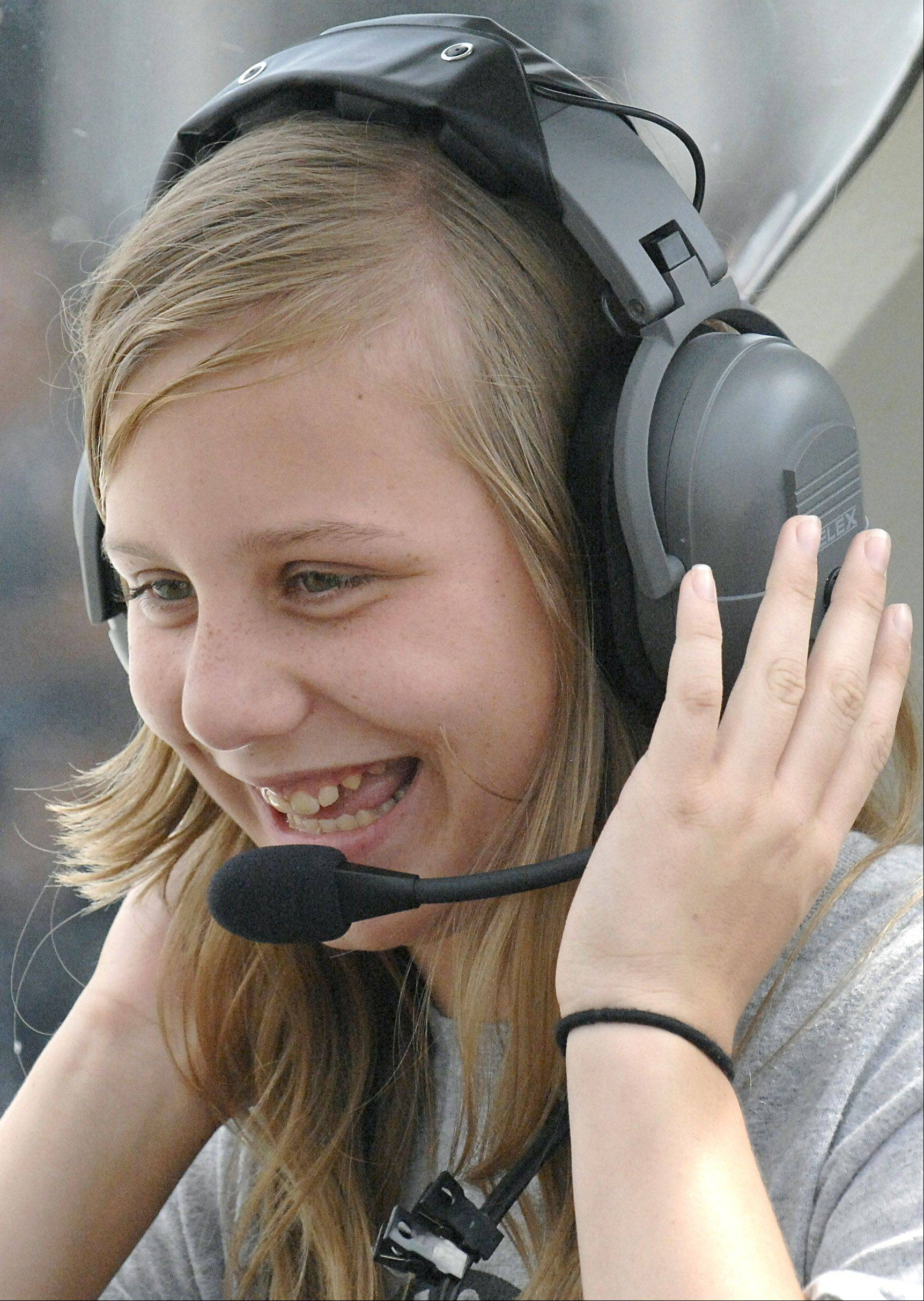 Morgan Hurley, 11, of Wentzville, Mo., giggles with excitement before taking off in Cary pilot Ole Sindberg's Prescott Pusher plane at Lake in the Hills Airport on Saturday. Hurley, joined by her twin sister, Paige, were visiting their cousin Lexi Yates, 9, of Crystal Lake and their grandparents Ray and Barbara Wolke of Chicago.