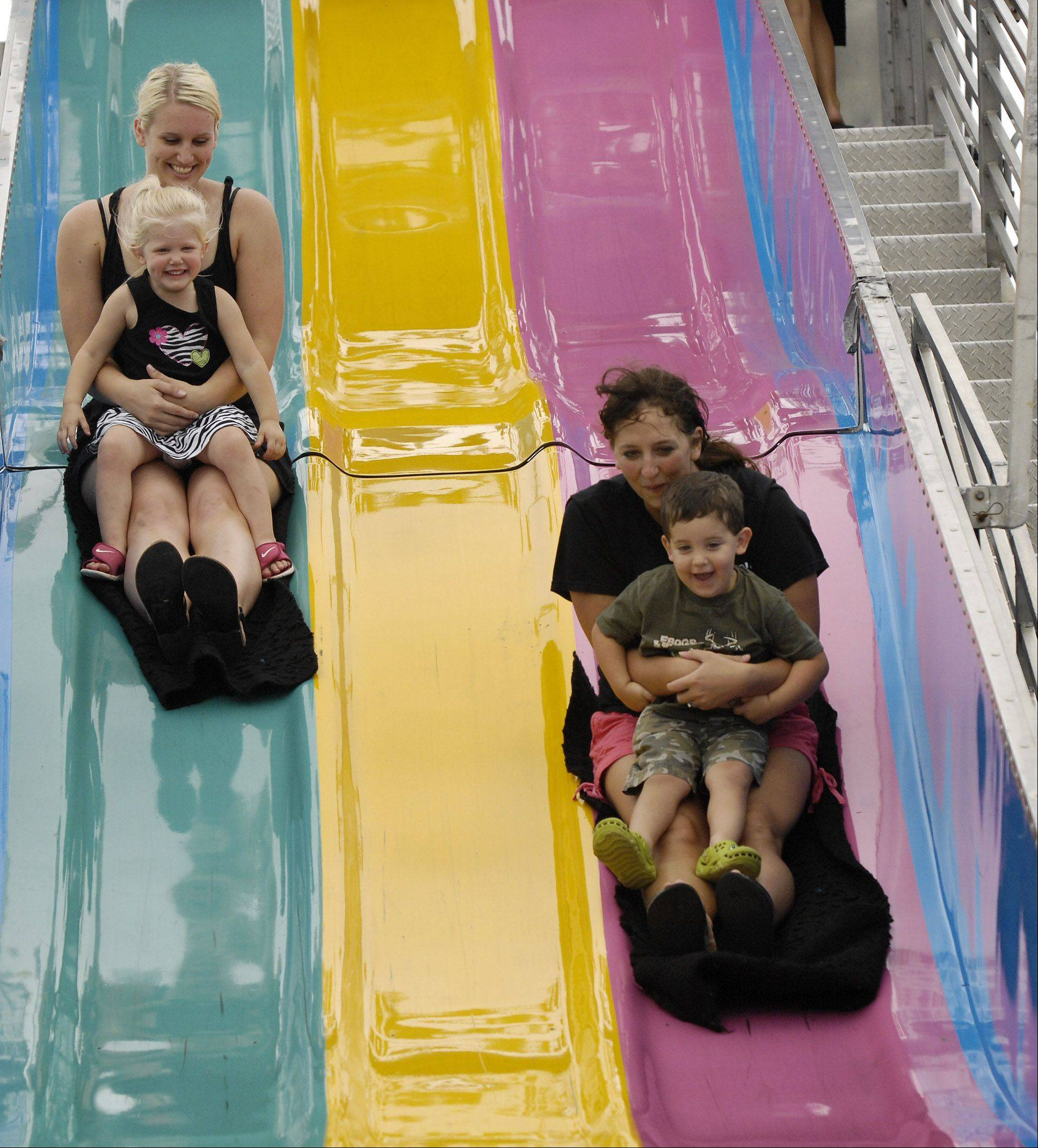 "Michelle and Cami Knox, 2, along with Ann and Rylan Mowers, 2, of Sycamore take a ride down the ""Fun Slide"" on the final day of the 2011 Kane County Fair in St. Charles."