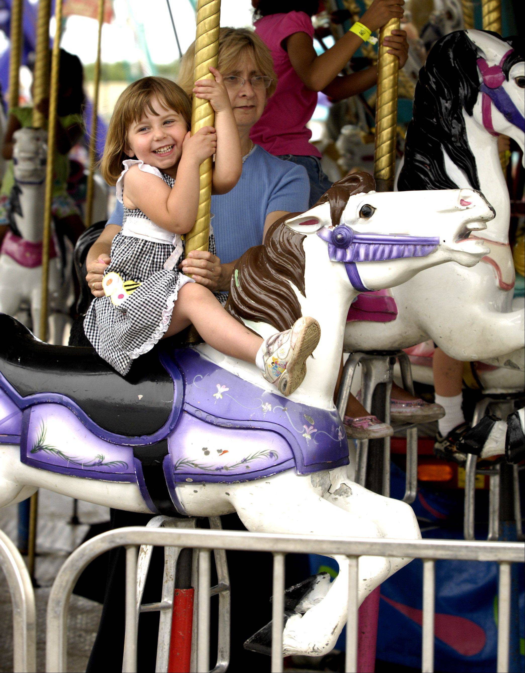 Lacey Brandstatt, 3, is all smiles as she rides the carousel with her grandmother, Laurie Brandstatt of Arlington Heights, on the final day of the 2011 Kane County Fair.