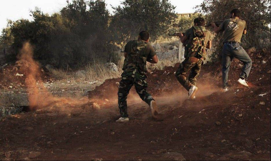 In this citizen journalism image taken on Friday, and provided by Edlib News Network ENN, Free Syrian Army soldiers aim their weapons in Idlib province, northern Syria.