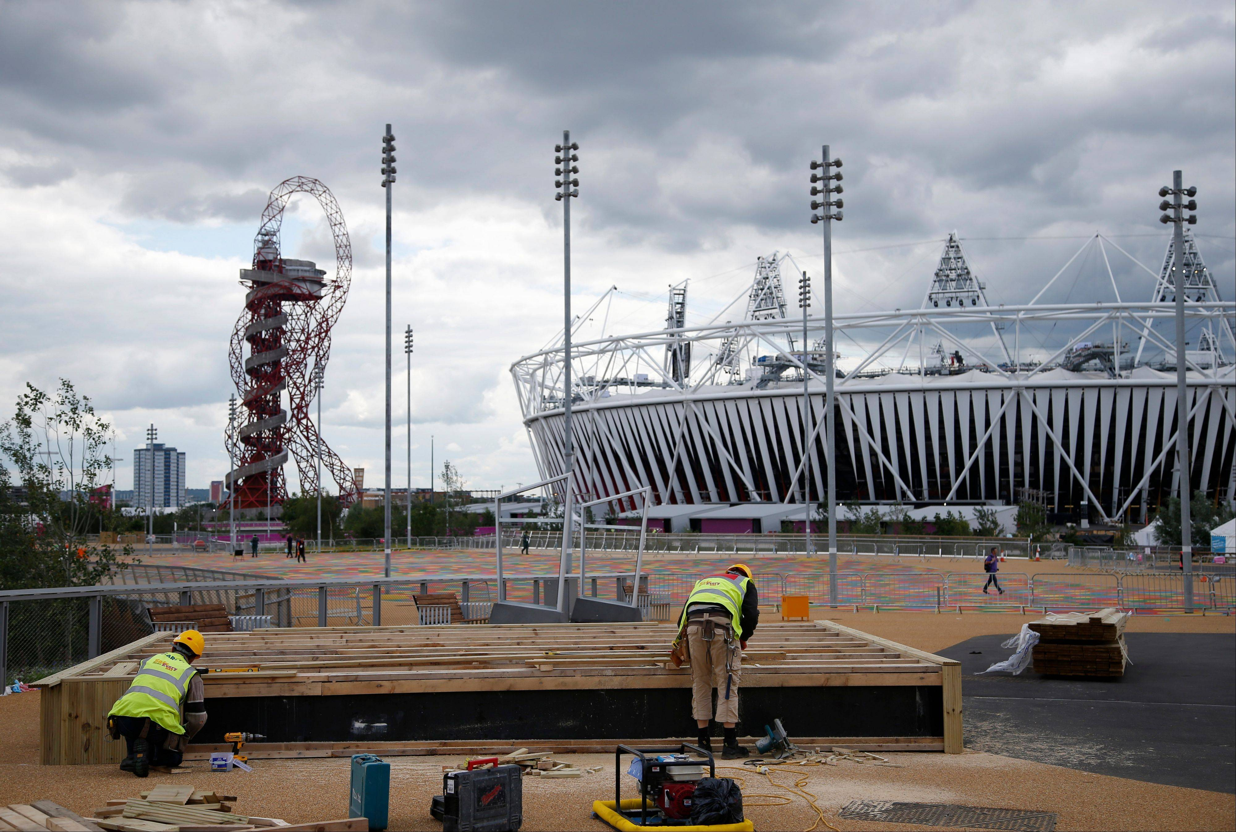 Construction crews work outside the Olympic Stadium Sunday as preparations continue for the 2012 Summer Olympics in London. At left is the Orbit.