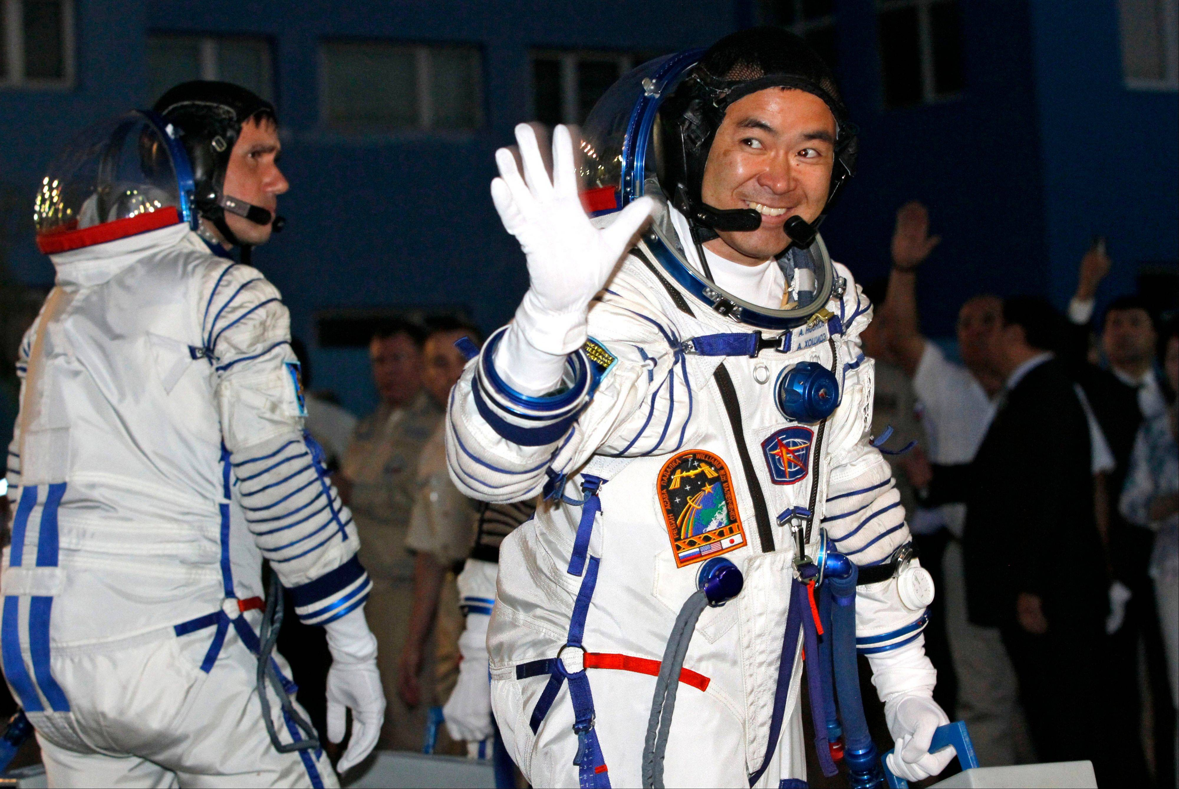 Russian cosmonaut Yuri Malenchenko, left, and Japanese astronaut Akihiko Hoshide, crew members of the mission to the International Space Station, ISS, gesture prior the launch of Soyuz-FG rocket Sunday at the Russian leased Baikonur cosmodrome, Kazakhstan.