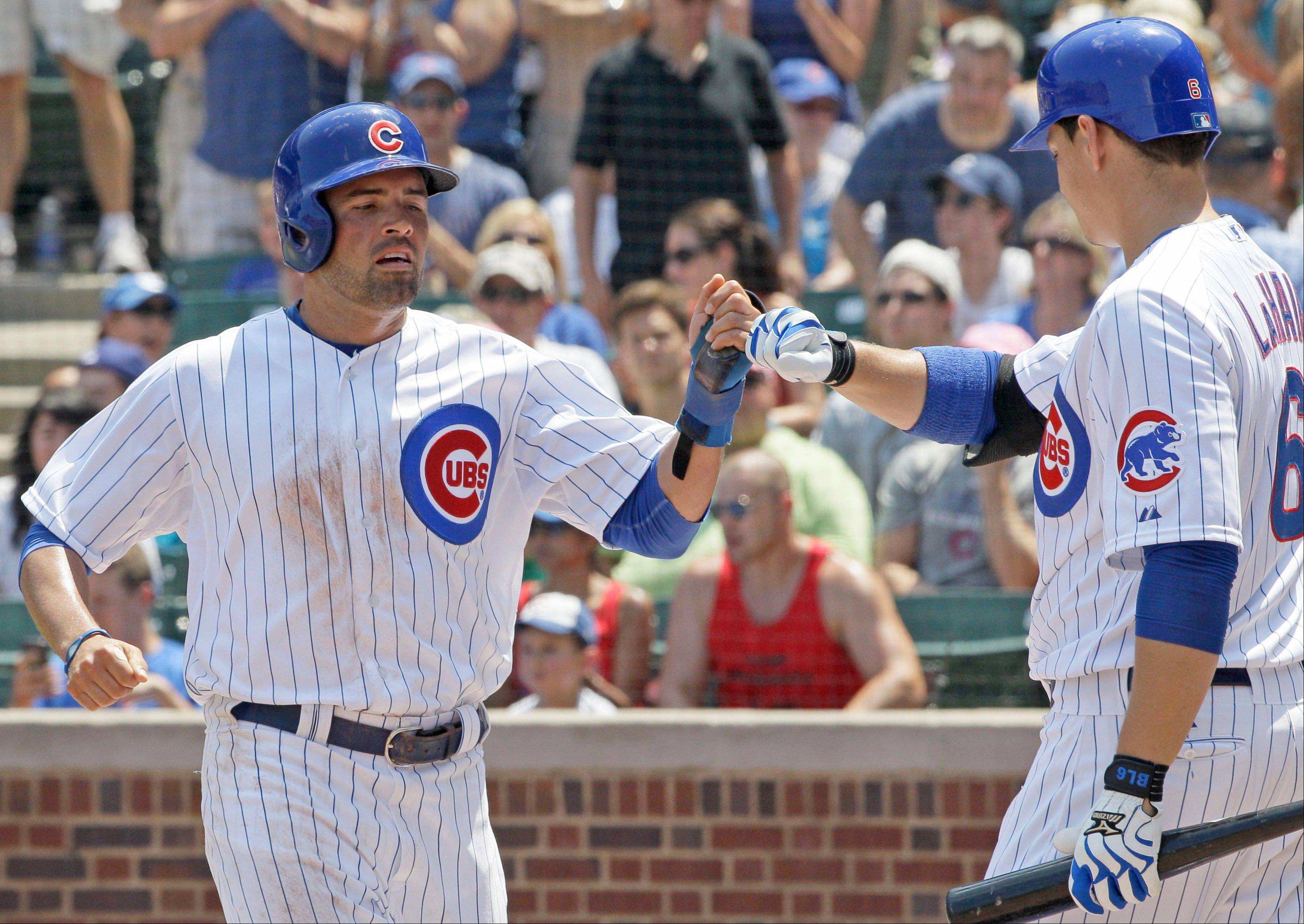 David DeJesus, left, celebrates with Bryan LaHair after scoring on a single hit by Anthony Rizzo during Sunday�s first inning of the Cubs� victory over Arizona at Wrigley Field.