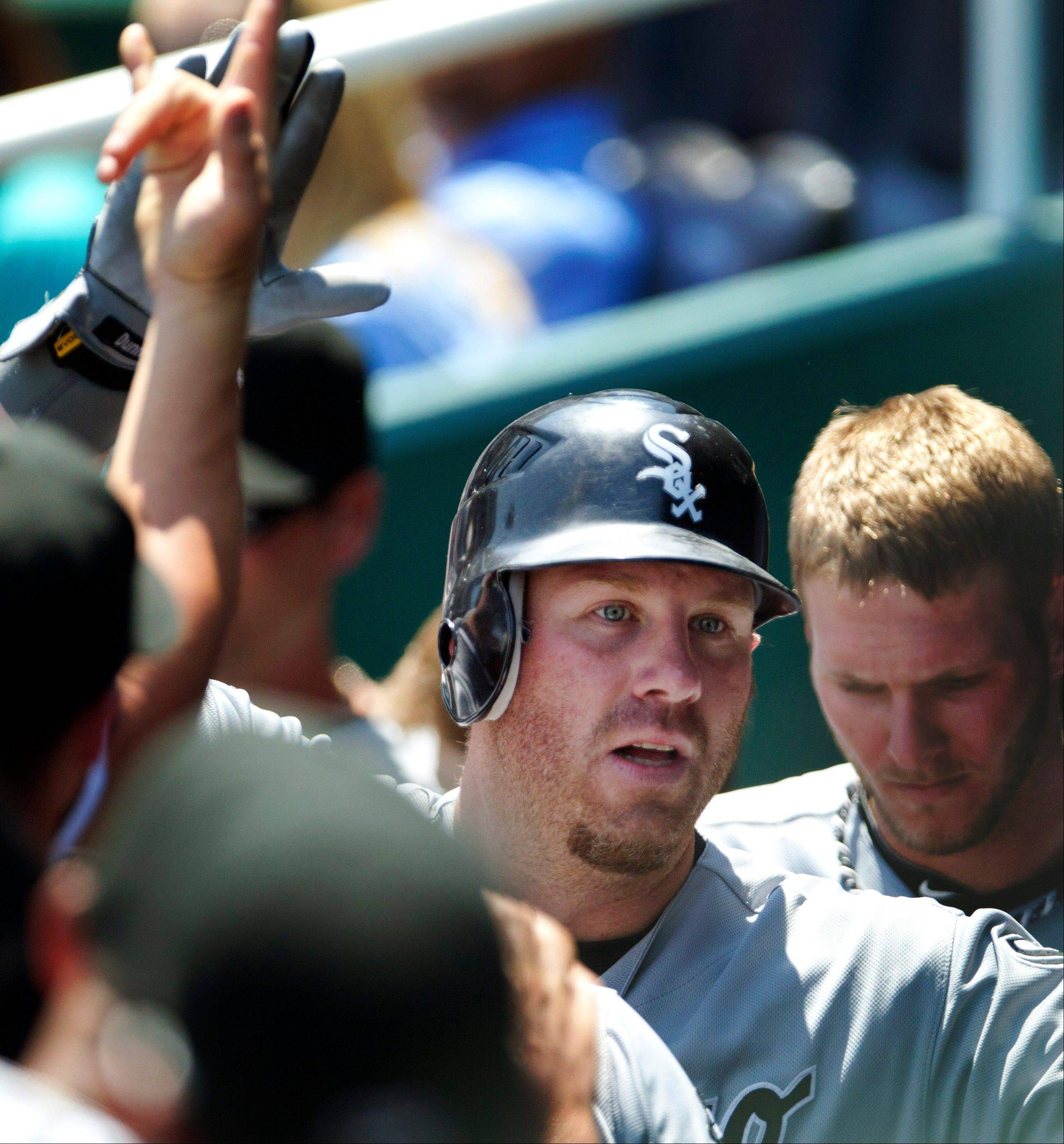 White Sox slugger Adam Dunn is congratulated by teammates Sunday after his solo home run off Kansas City Royals starting pitcher Luis Mendoza in the first inning at Kauffman Stadium.