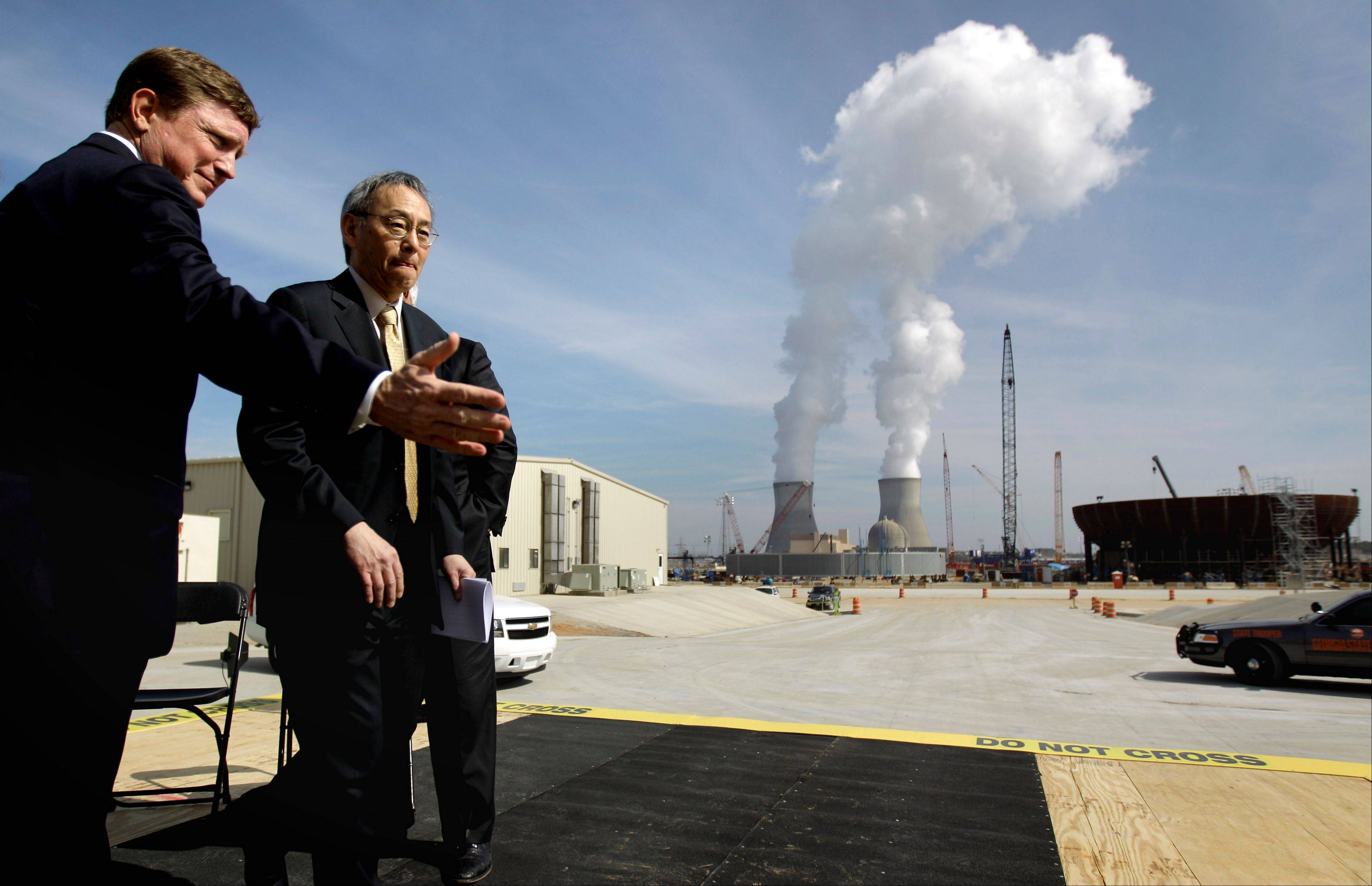 U.S. Secretary of Energy Steven Chu, right, exits the stage with Southern Co. President and CEO Thomas Fanning on Feb. 15 as cooling towers for units 1 and 2 are seen in the background at left and the new reactor vessel bottom head for Unit 3 stands under construction at right. Chu visited the Vogtle nuclear power plant in Waynesboro, Ga. Vogtle, initially estimated to cost $14 billion, has run into more than $800 million in extra charges related to licensing delays. A state monitor has said bluntly that co-owner Southern Co. can't stick to its budget. The plant, whose first reactor was supposed to be operational by April 2016, is now delayed seven months.