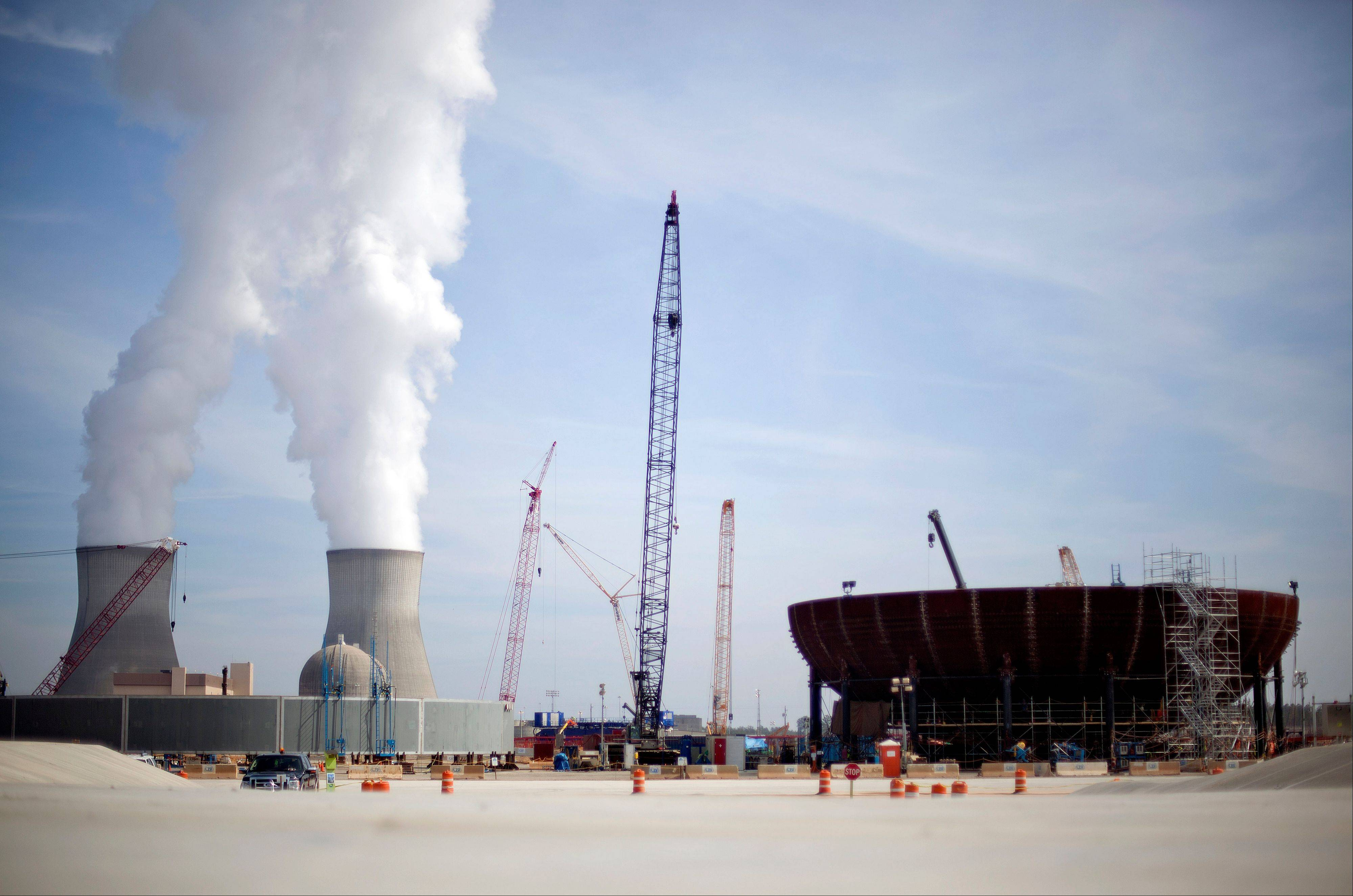 Cooling towers for units 1 and 2 are seen at left as the new reactor vessel bottom head for Unit 3 stands under construction at right at the Vogtle nuclear power plant in Waynesboro, Ga., on Feb. 15. Vogtle, initially estimated to cost $14 billion, has run into more than $800 million in extra charges related to licensing delays. A state monitor has said bluntly that co-owner Southern Co. can't stick to its budget. The plant, whose first reactor was supposed to be operational by April 2016, is now delayed seven months.