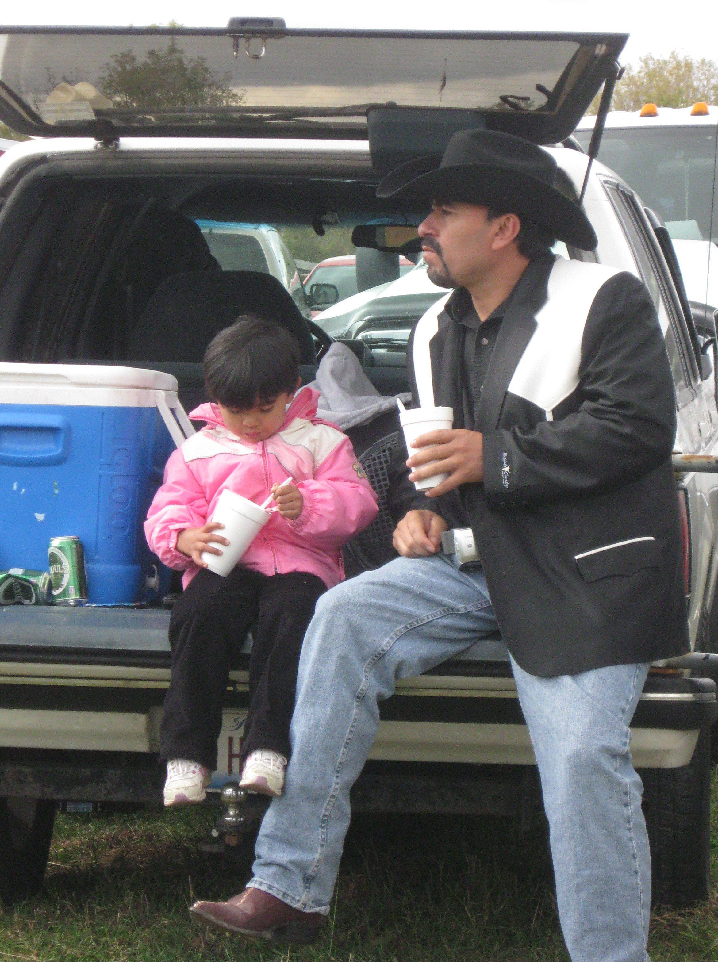 José Rivera and his daughter, Starlight, of Crystal Lake take a break from horse races at Poker de Ases Ranch and Training Center in Union. Each race lasts about 14 seconds, with 30 minutes between races to eat and mingle with friends.