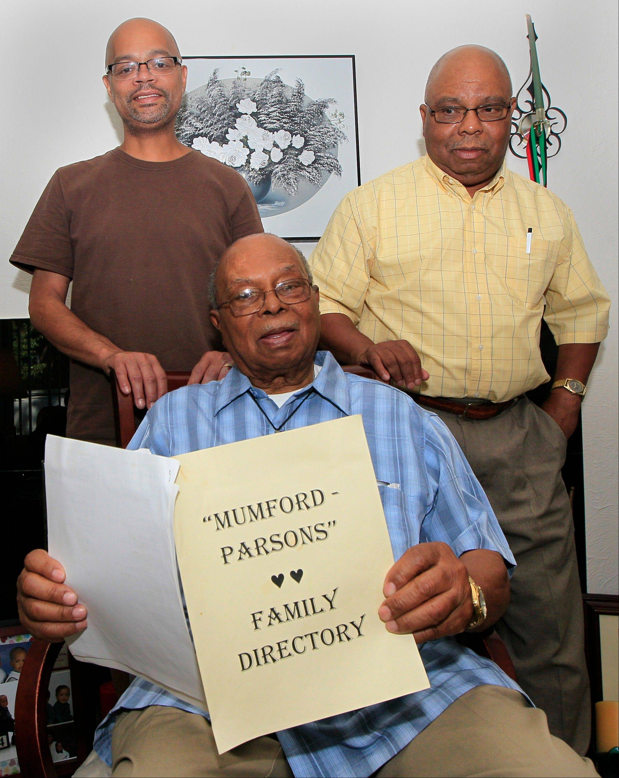 Jewell Wilson, foreground, great-grandson of former slave Jordan Anderson, holds a family directory June 25 as he poses with his son, Jewell Wilson Jr., left, and his nephew Barry Mumford Wilson in Dayton, Ohio. Anderson, who wrote a remarkable letter to his ex-master, was freed from a Tennessee plantation by Union troops in 1864 and spent his remaining 40 years in Ohio.