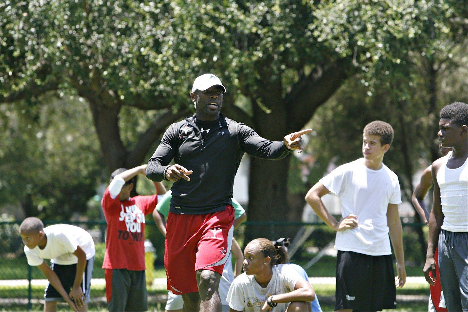 Andre Hudson explains the next drill for athletes he coaches in a summer strength training and conditioning camp called Lives Under Construction at St. Petersburg's Lake Vista Park.