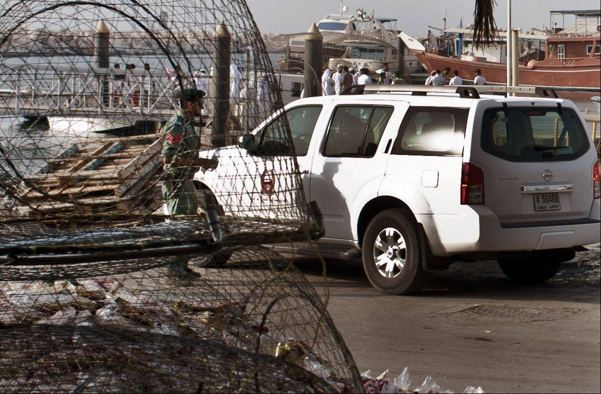 Emirati police and other officials inspect a boat docked in a fishing harbor in the Jumeirah district of Dubai, United Arab Emirates, Monday. A U.S. official in Dubai says an American vessel has fired on a boat off the coast of the United Arab Emirates, killing one person and injuring three.