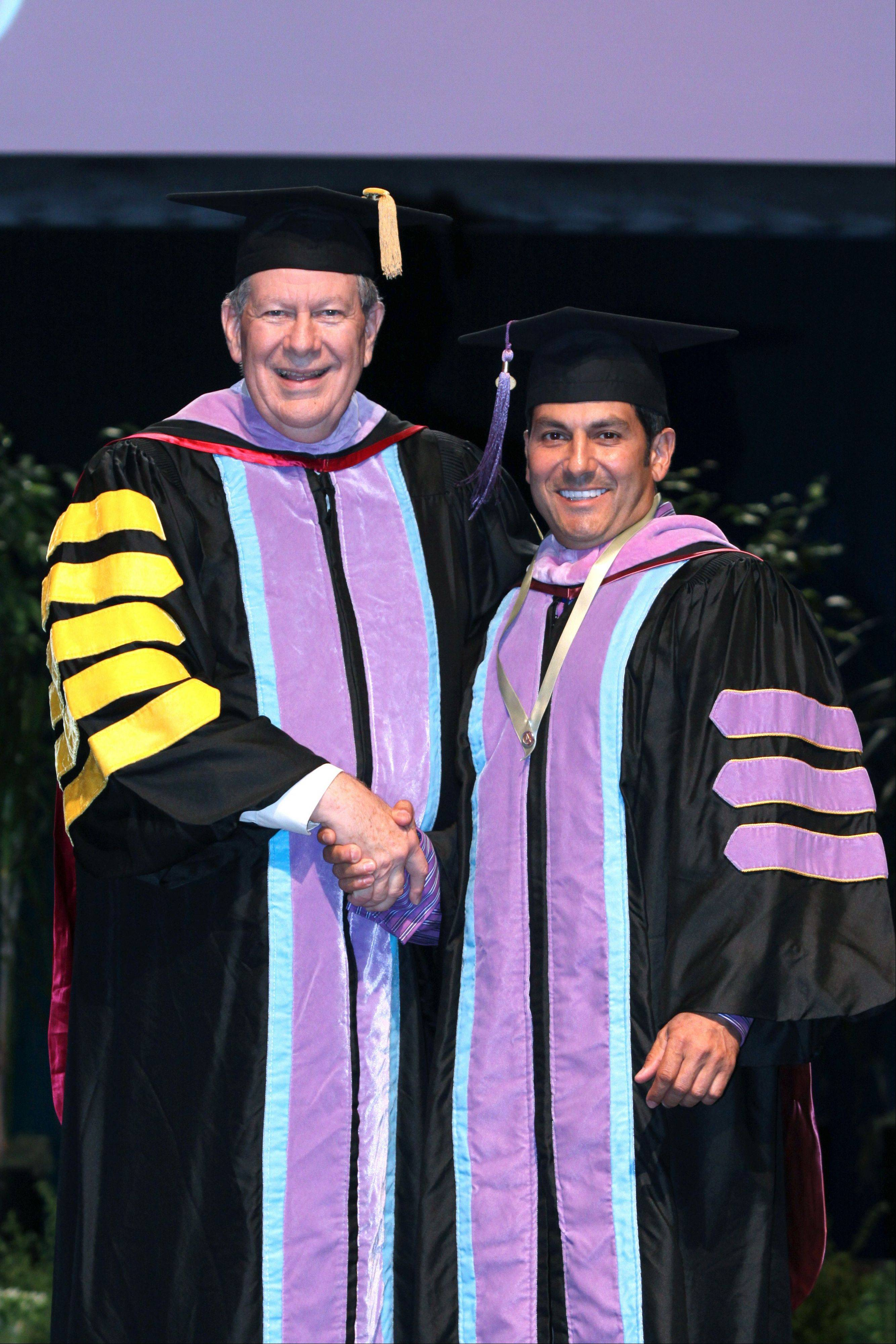 Michael R. Errico, at right, receives the Academy of General Dentistry's 2012 Fellowship Award from Jeffrey M. Cole, (with gold bars on the gown) president of the organization.